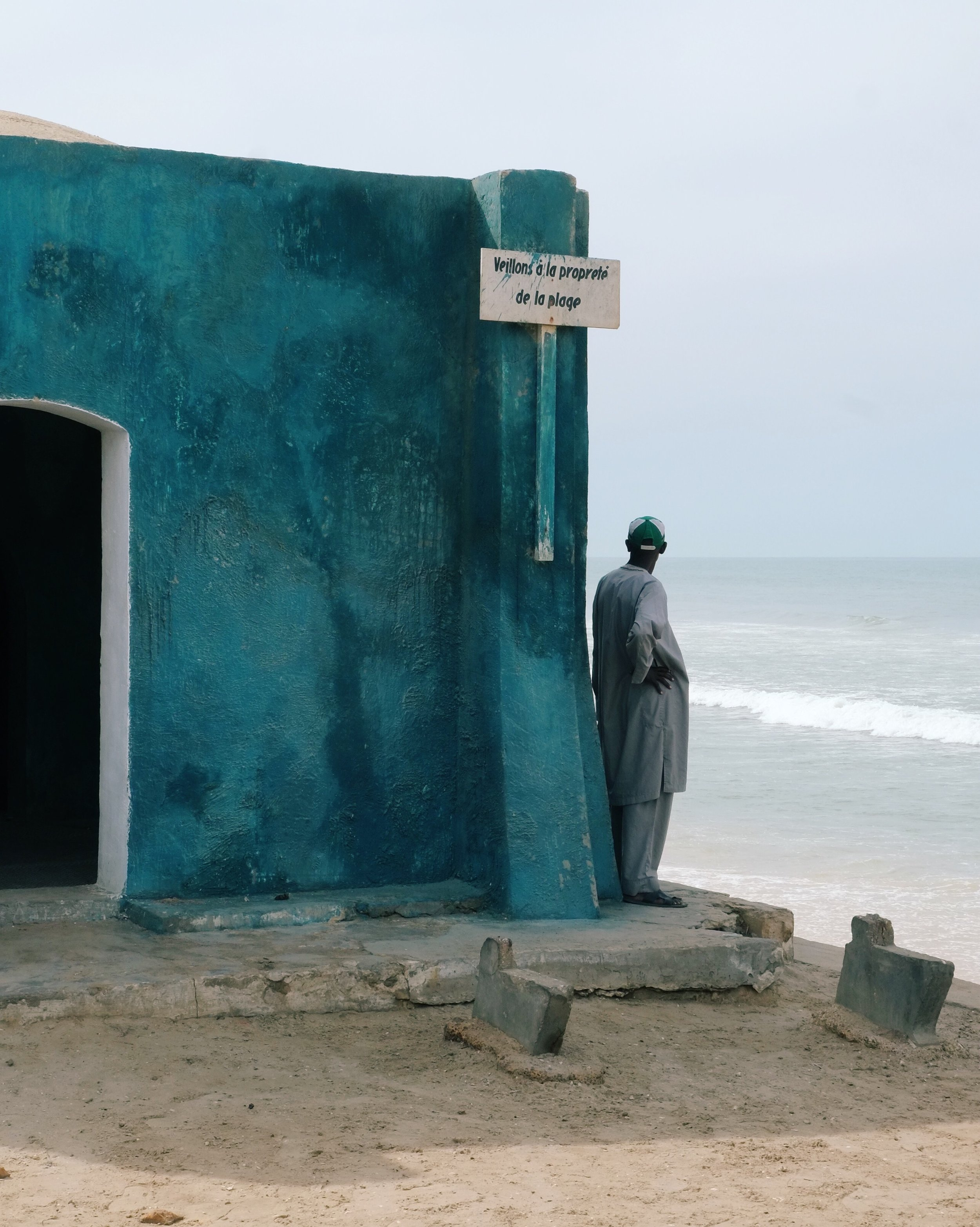 A man looks at the crumbling shores of Saint-Louis, Senegal.jpg