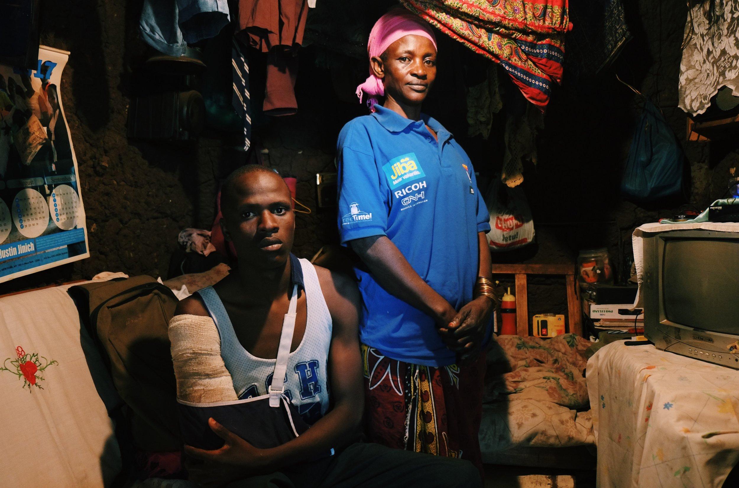 Jackton shows his shot arm in his house in Kibera Kenya.jpeg