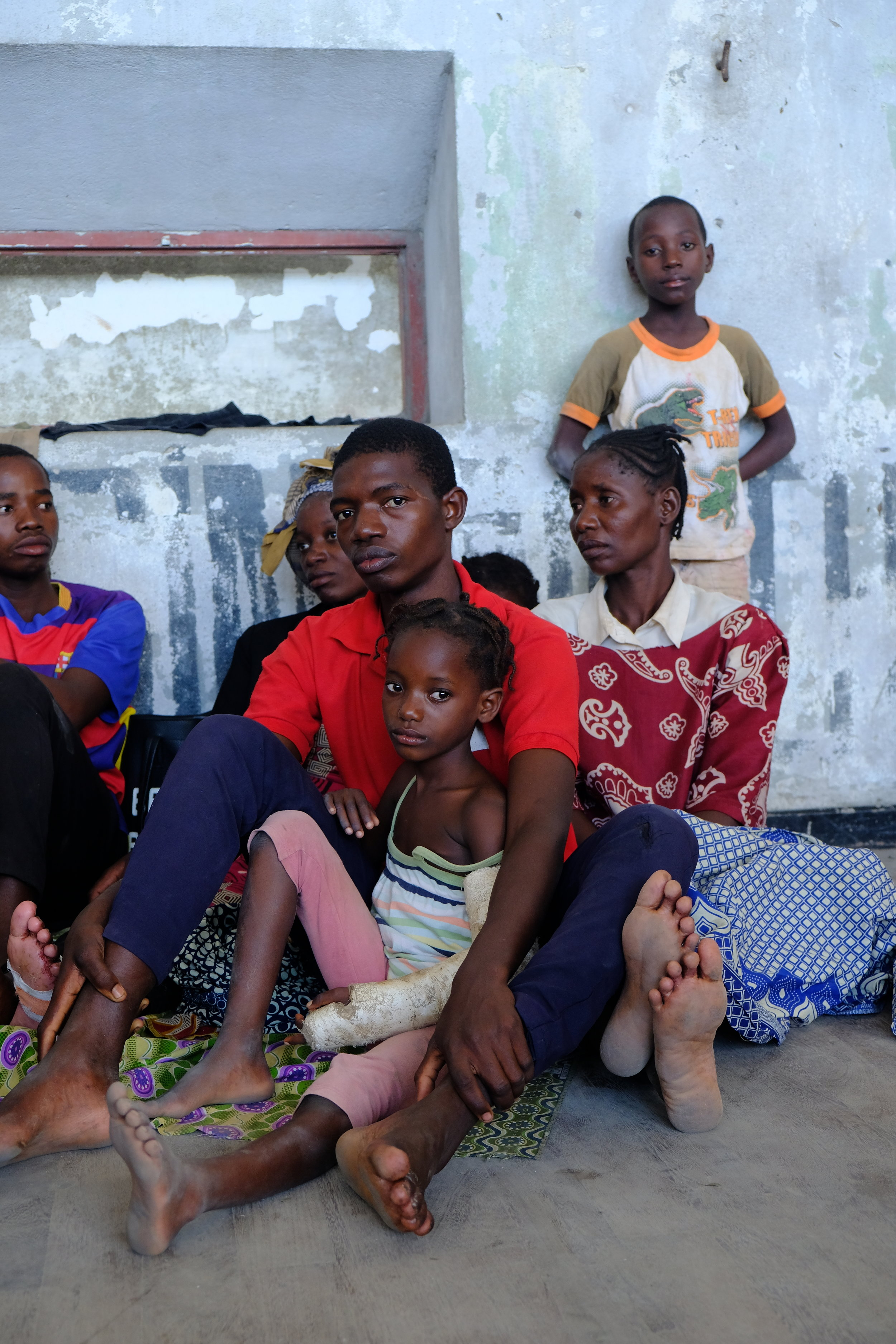 A family sits against the wall of a Beira shelter.JPG