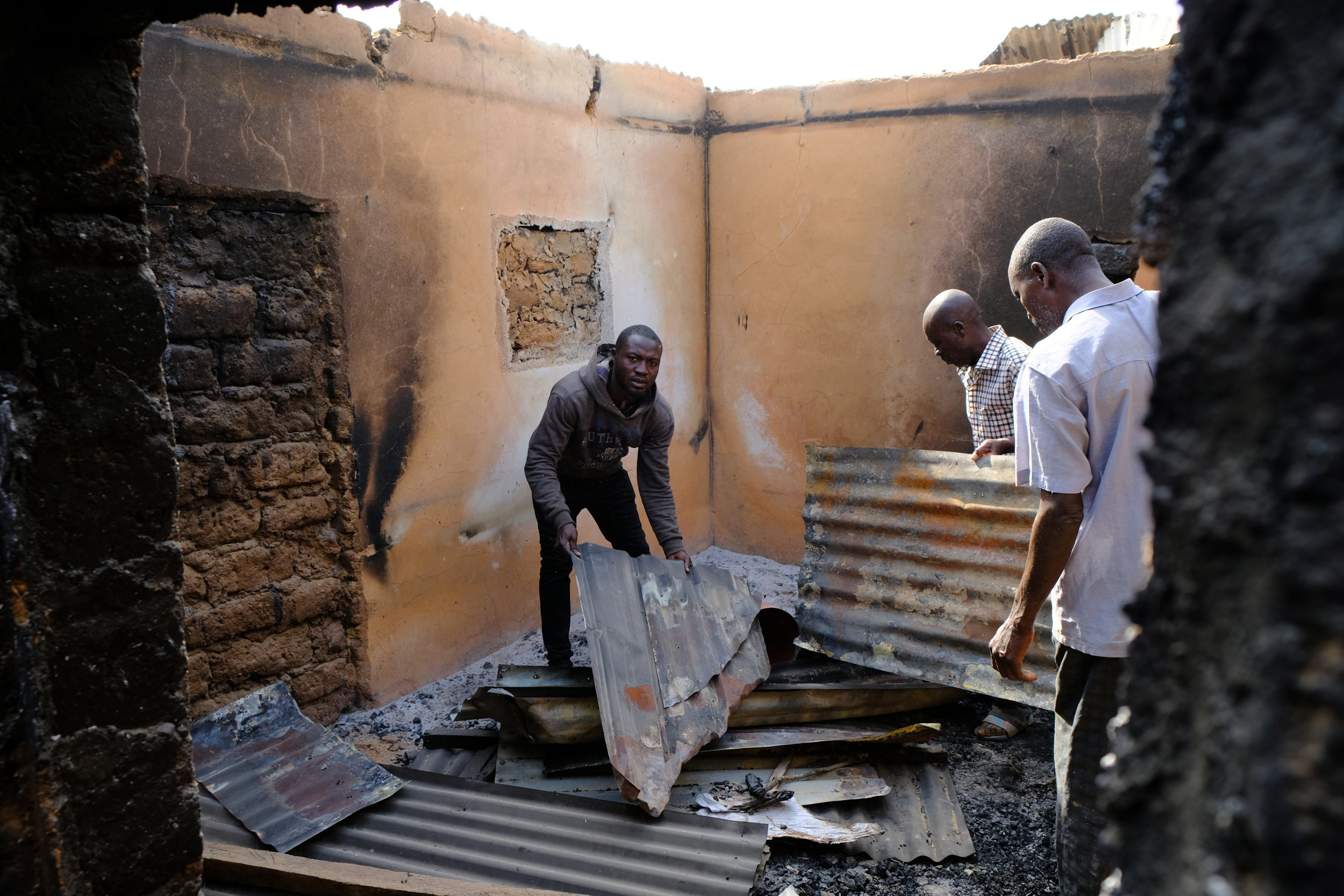 Villagers look for their belongings in between the burnt rubble.JPG