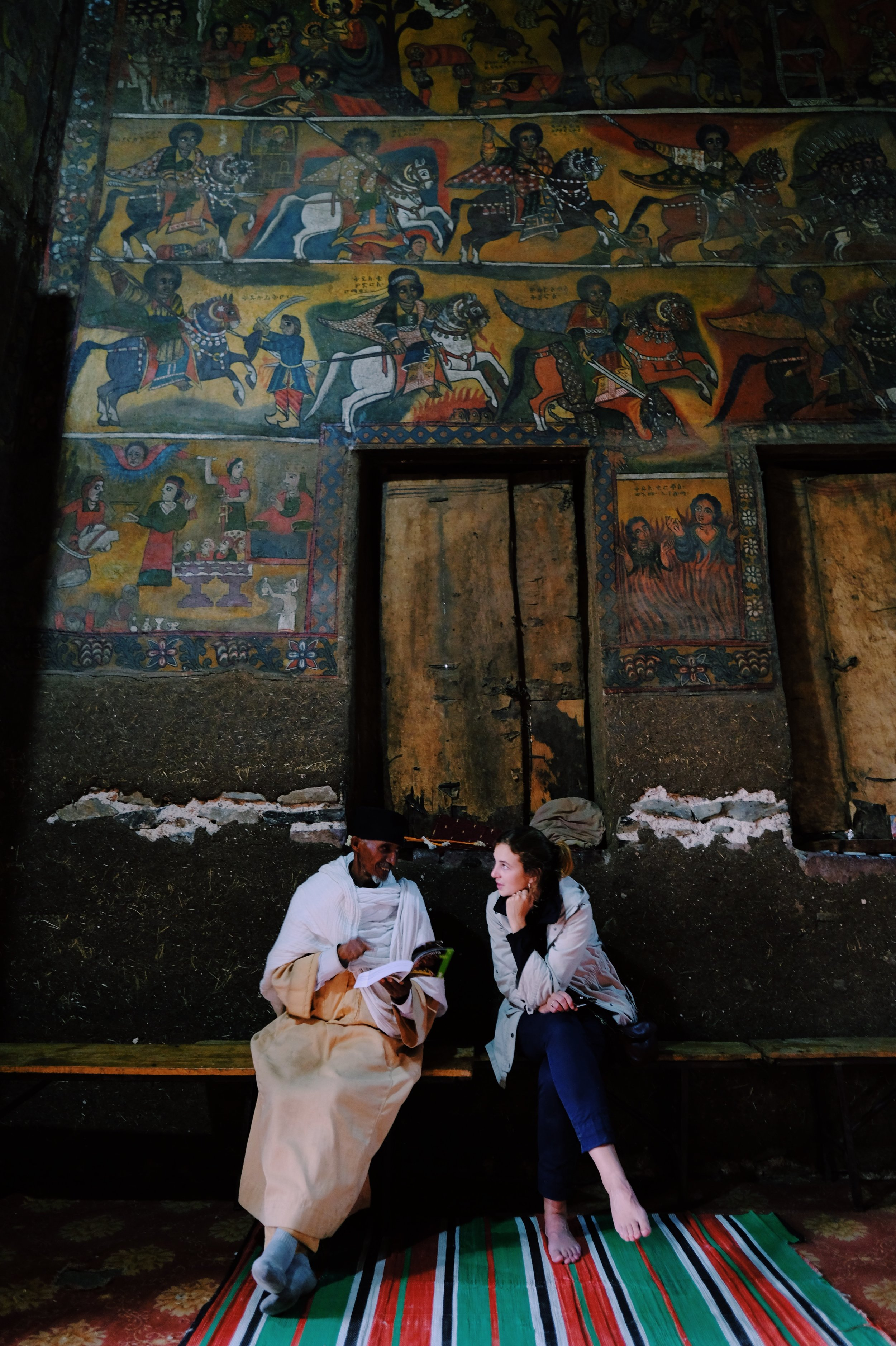Saskia and a Gondar priest are discussing pictures in the Ethiopia Bradt guide.jpg