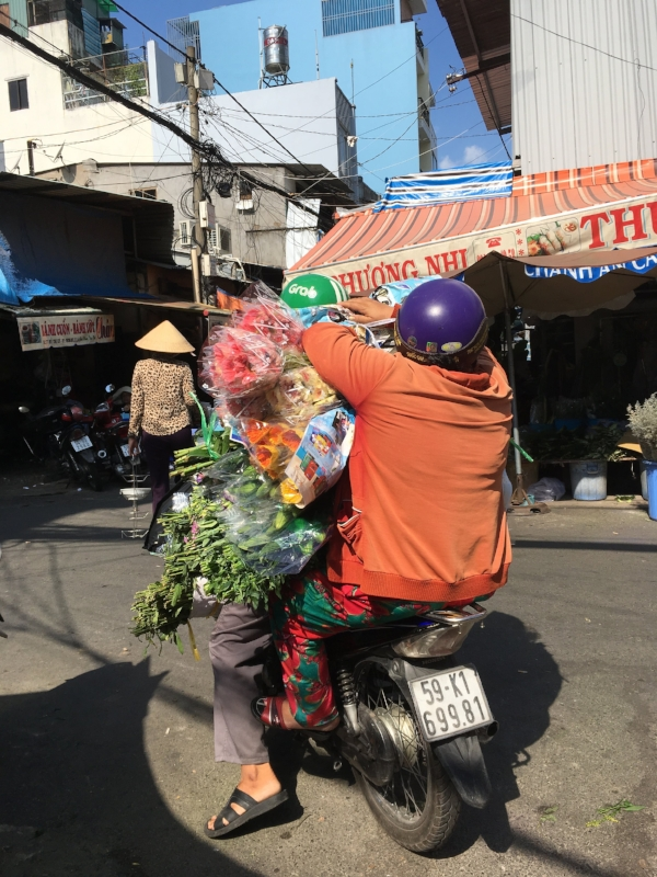 This woman had just bought a shops worth of flowers at the wholesale market. She hopped on a motorbike taxi (note GRAB on the drivers helmet) and headed off with her load!