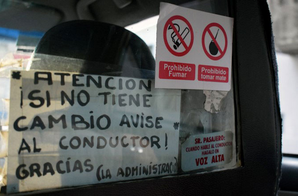 These two signs plastered to the plexiglass read: Attention! if there is no change notify the driver. Huh? The second one reads Mr. Passenger: When you speak do it loud. No kidding.