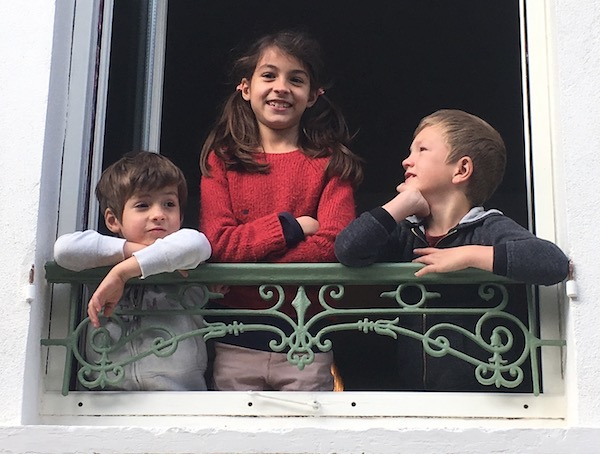 The grandchildren waiting at the window of their house around the corner.