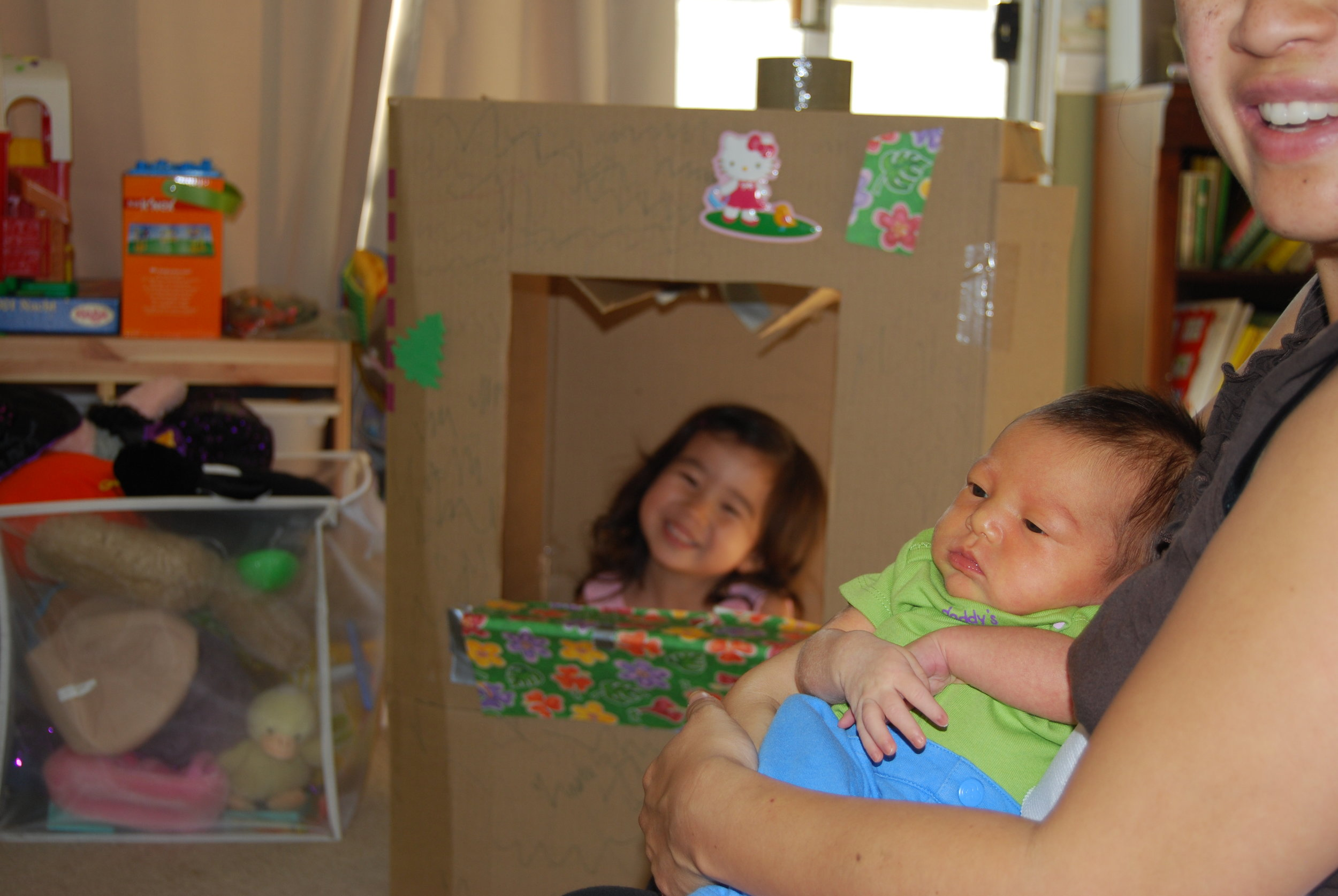 Mini Me playing in her bakery box while I snuggle up with a newborn Little Lion.  See, she's even yellow! (with jaundice) Posted with permission.