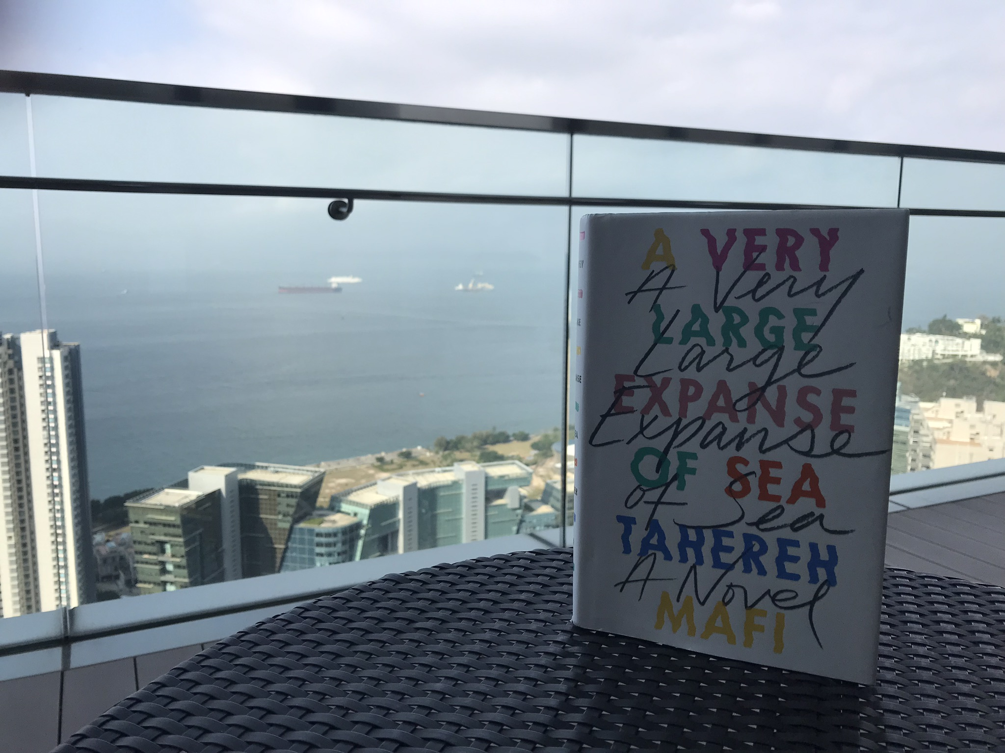 Tahereh Mafi's A Very Large Expanse of Sea pictured with the South China Sea in the background. Top picture taken by my dad, both pictured in Hong Kong.