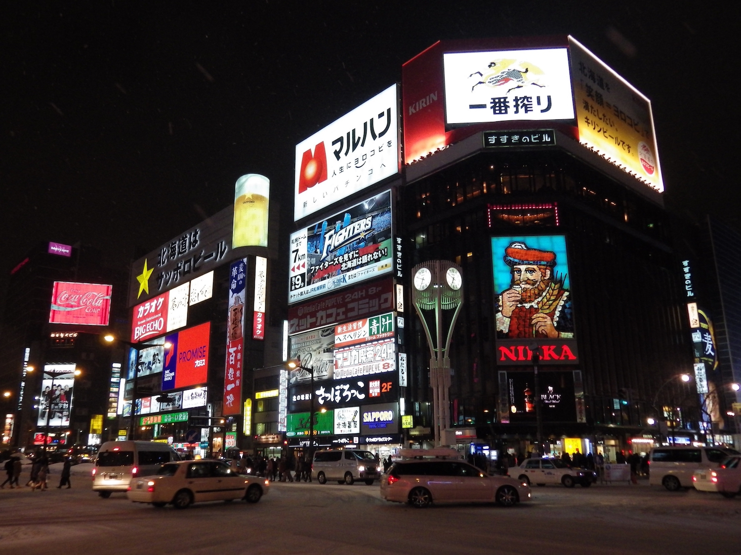 Susukino Crossing at night, with Nikka Whiskey's King of Blenders sign visible on the side of the Susukino Building.