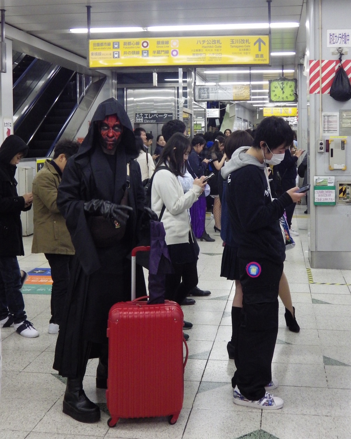 Cosplayer dressed as Darth Maul, waiting to catch a JR Yamanote Line train in Shibuya Station, on Halloween Night 2015.