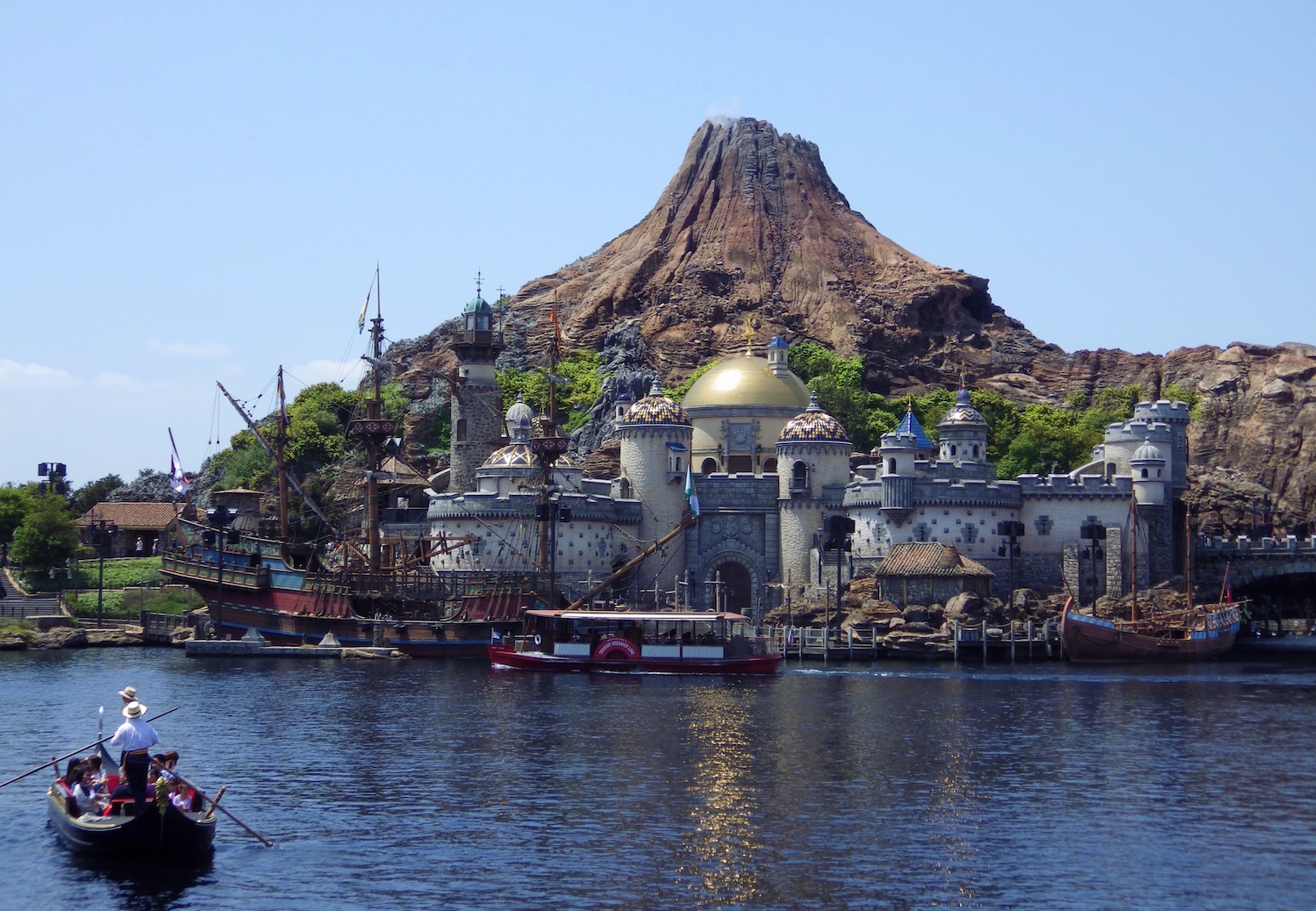 A Venetian Gondola passes in front of Mount Prometheus in Mediterranean Harbor at Tokyo DisneySea.