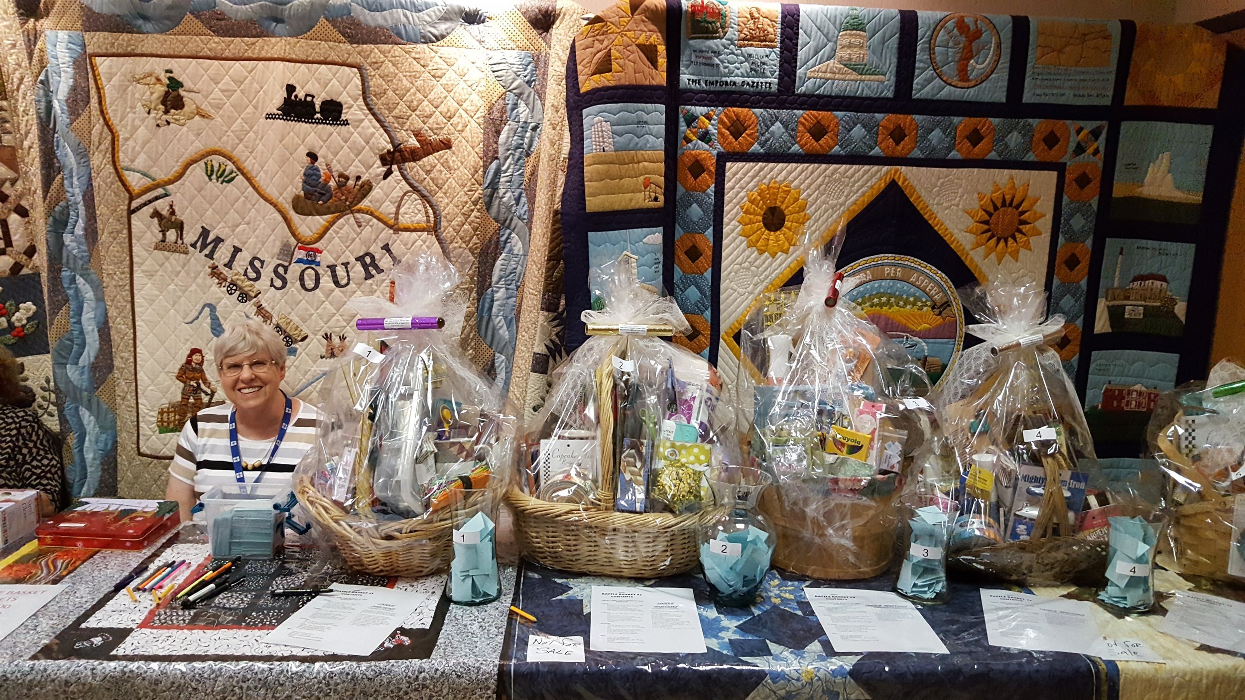 Guild Quilts above raffle baskets