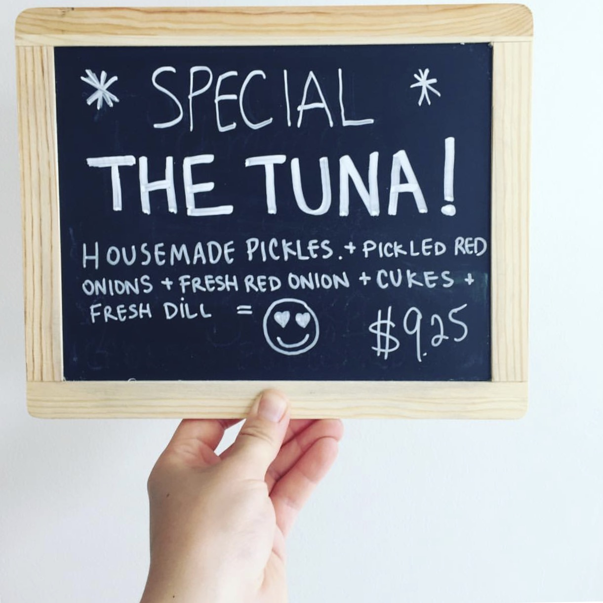 """Photo cred  Lox + Schmear Instagram   Accessibility [Photo Description: small chalkboard with the message """"Special The Tuna, house made pickles + pickled red onions + fresh red onion + cukes + fresh dill = heart eyes smiley face emoji $9.25]"""
