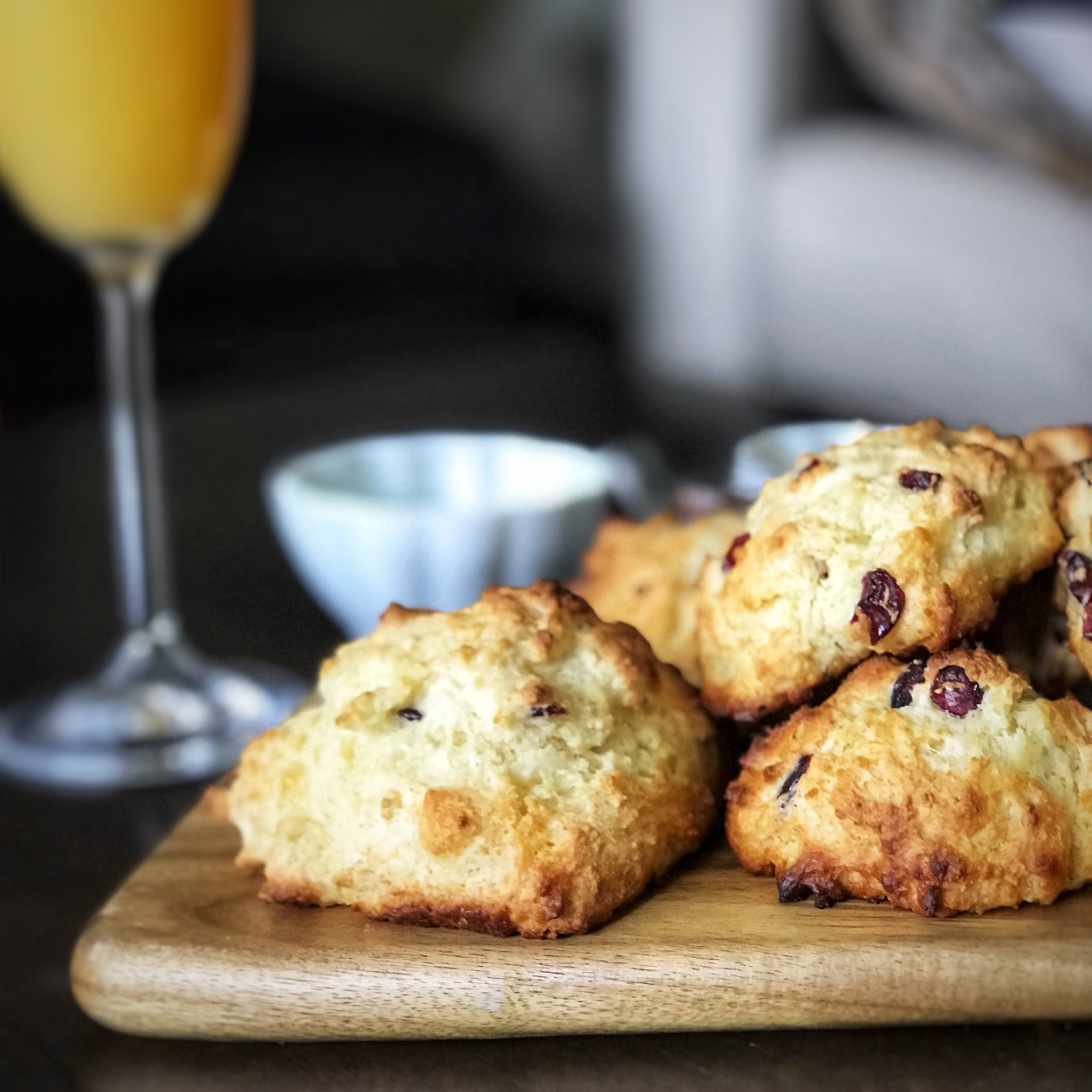 Photo Description: Champagne glass filled with mimosa, a small bowl, in the background. In the forefront, a wood serving board with several roundish cranberry eggnog scones resting on top.
