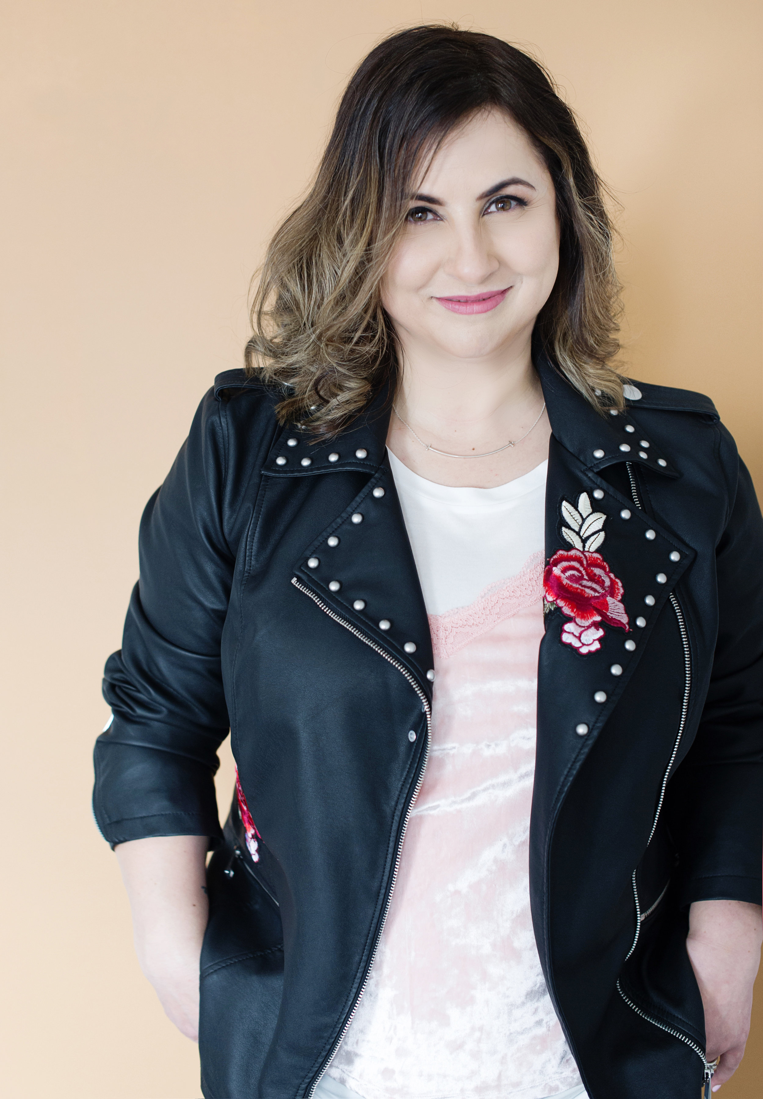 Photo Description: Mary smiling, head tilted to the camera, wearing a studded leather jacket, t-shirt and smile necklace