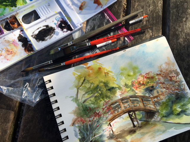 Bridge in the Japanese Garden, along with my watercolor palette and brushes. ©2016 by Erin Blumer.