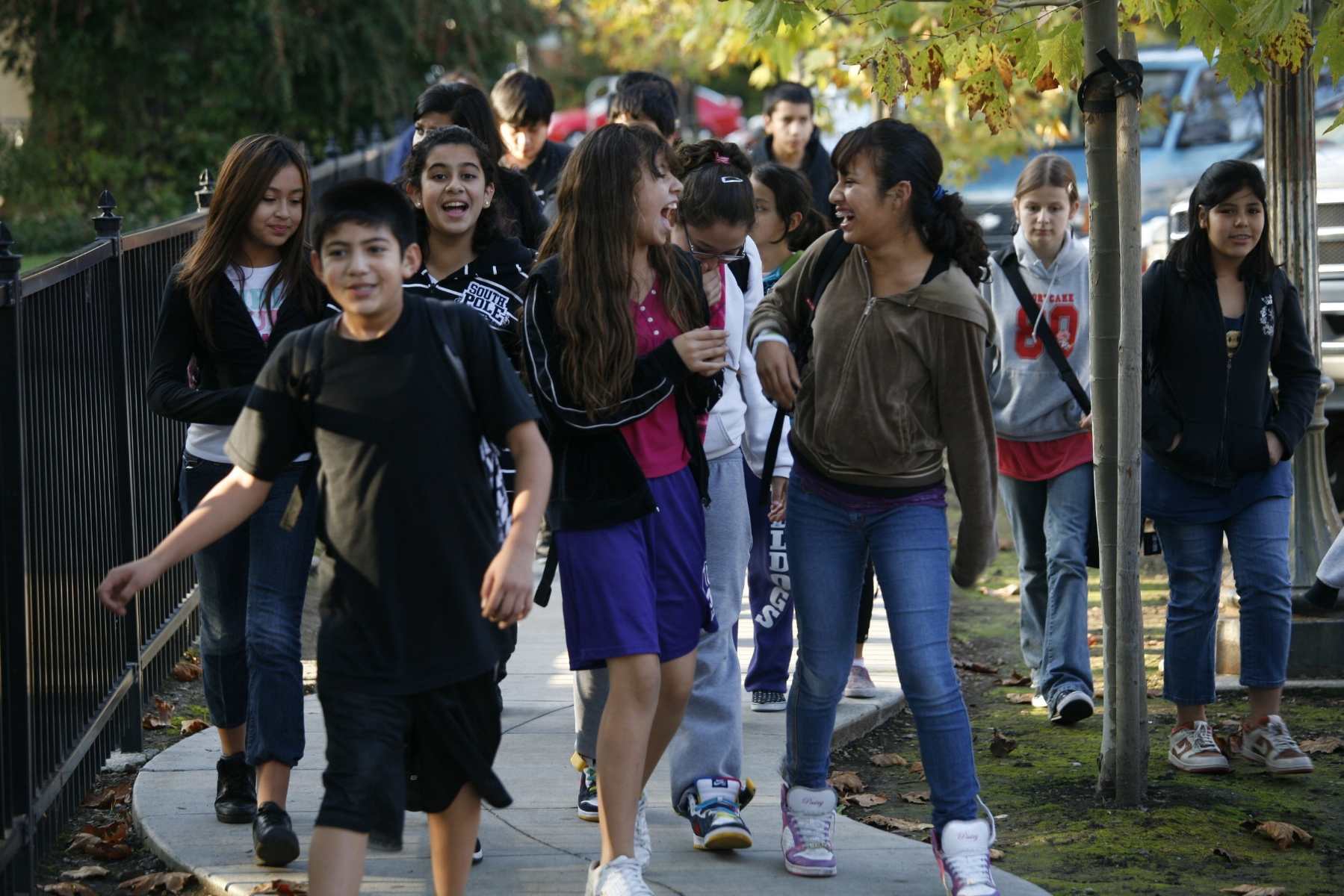 a group of students are walking on a sidewalk and looking like they are having fun.  two girls are the center of the composition.  the two are looking at each other and have big smiles. They are clearly friends and laughing together.