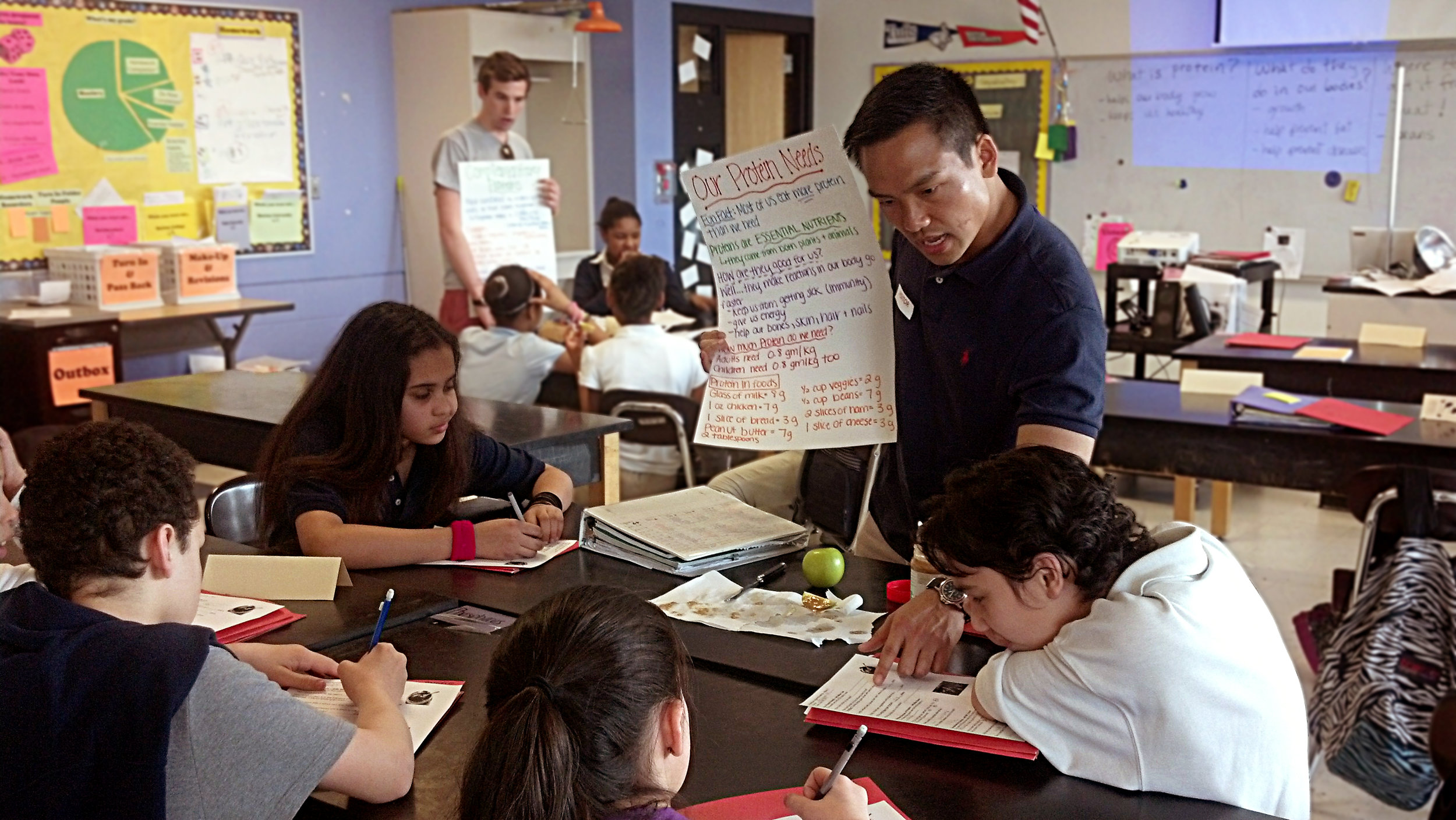 a citizen teacher volunteer is holding a large piece of paper that has nutrition facts written on it.  he is pointing to a worksheet that a student is working on while other students are working nearby.