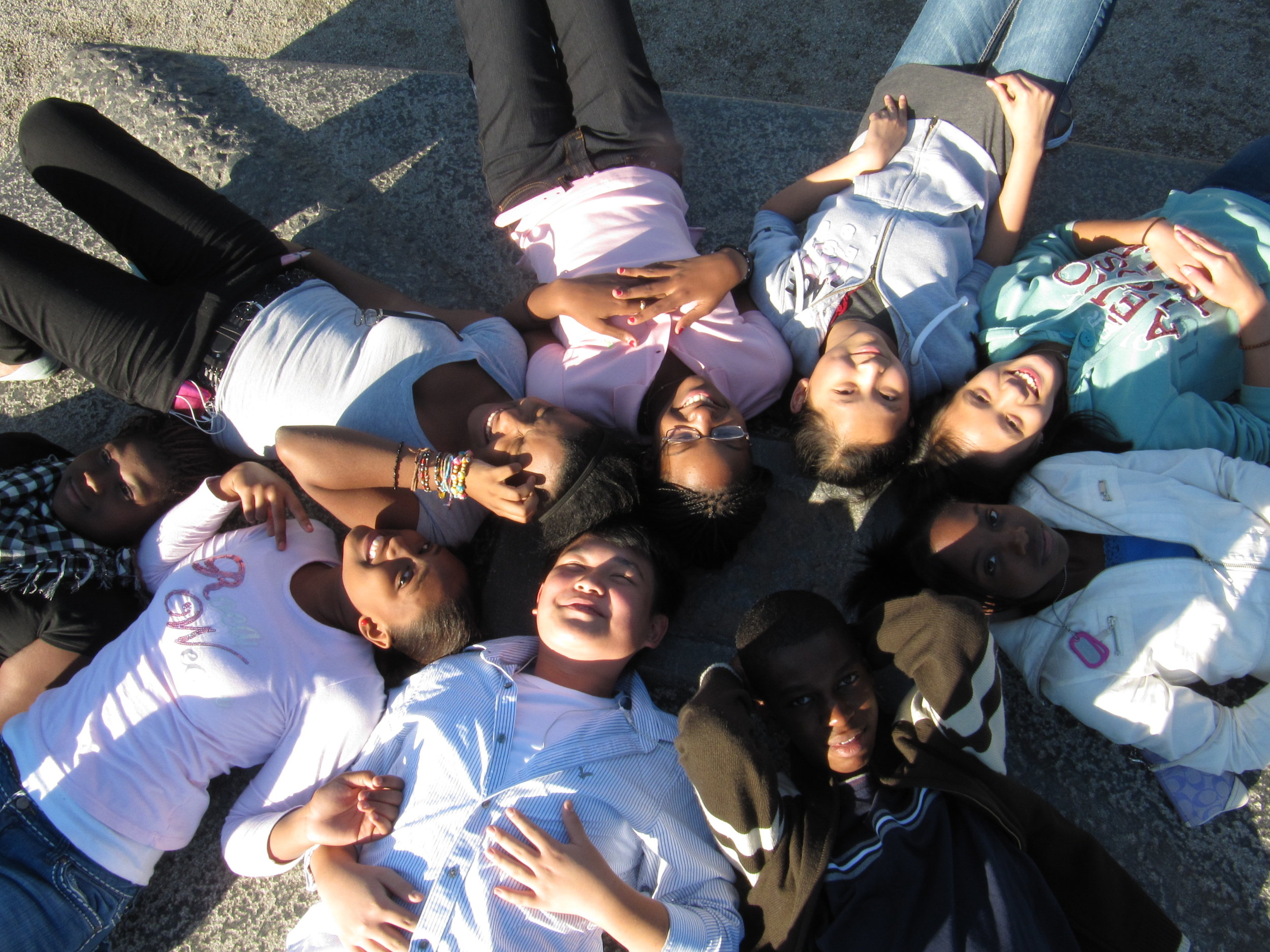 a group of kids are laying on the ground with their heads in a circle smiling at the camera.