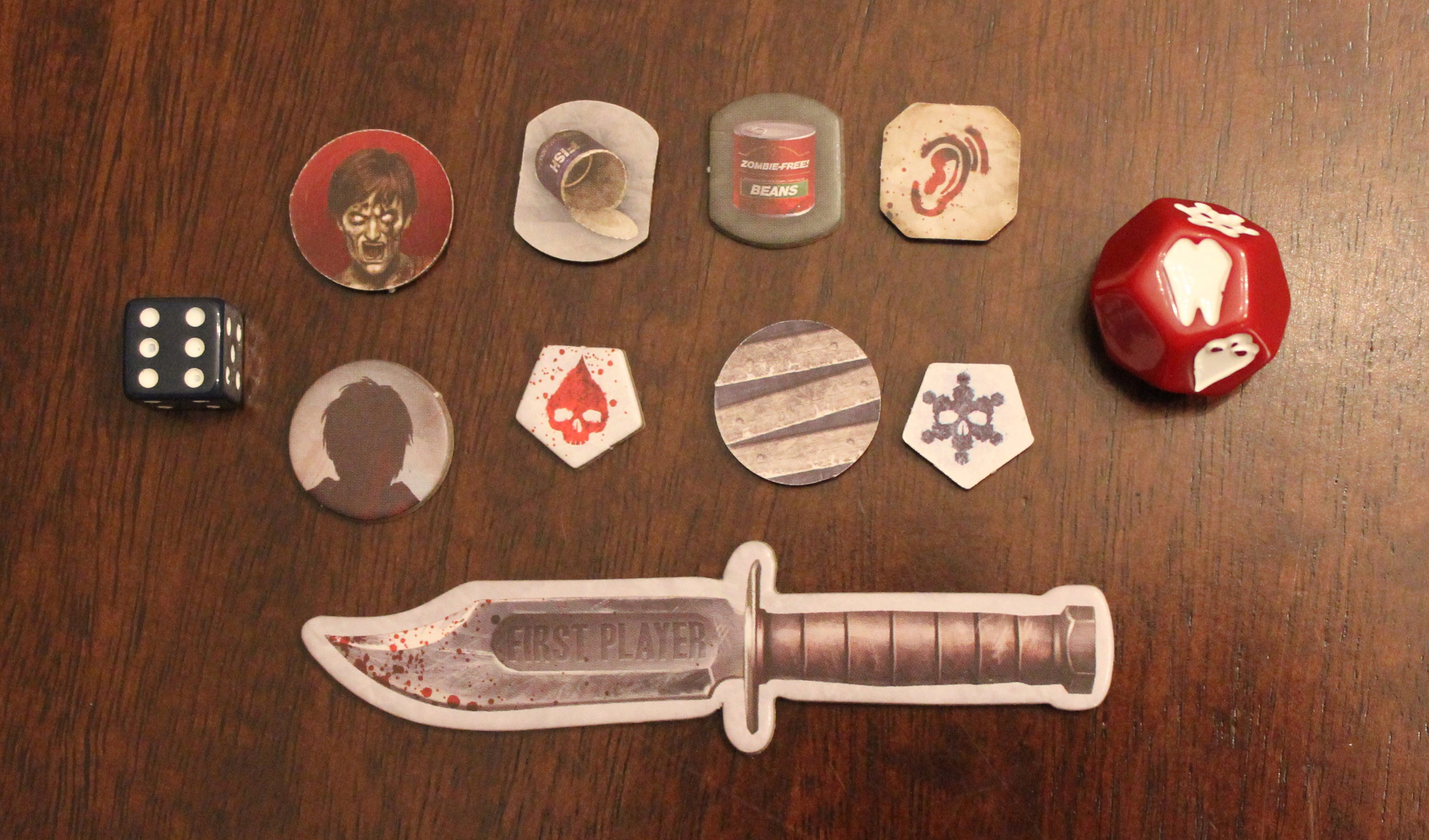 Exposure die is the red one on the right. Also pictured, the knife to indicate first player and the various tokens used throughout the game.