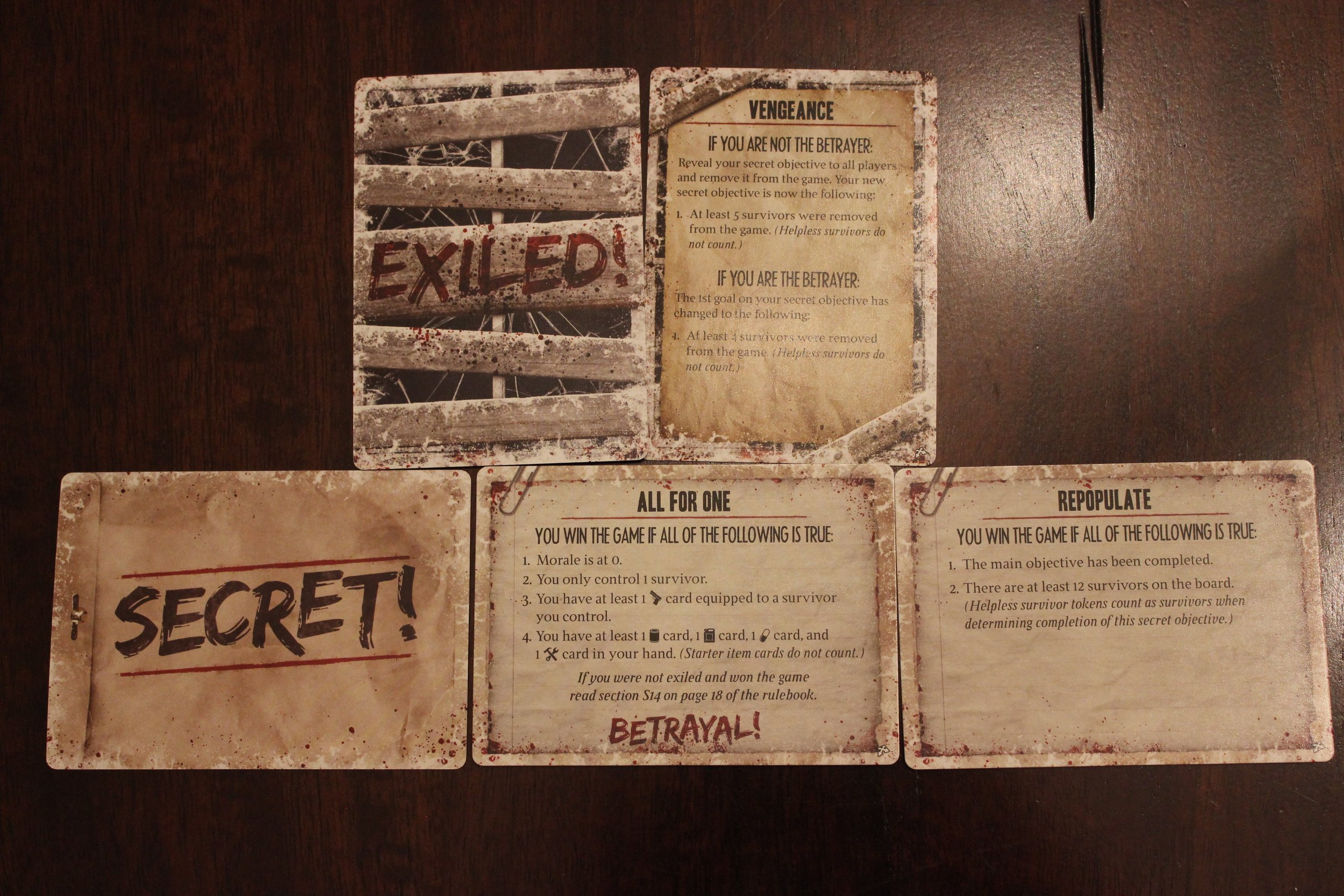 Top row: Sample exile card if a player is exiled. Bottom row: Samples of a traitor and normal secret objective card.