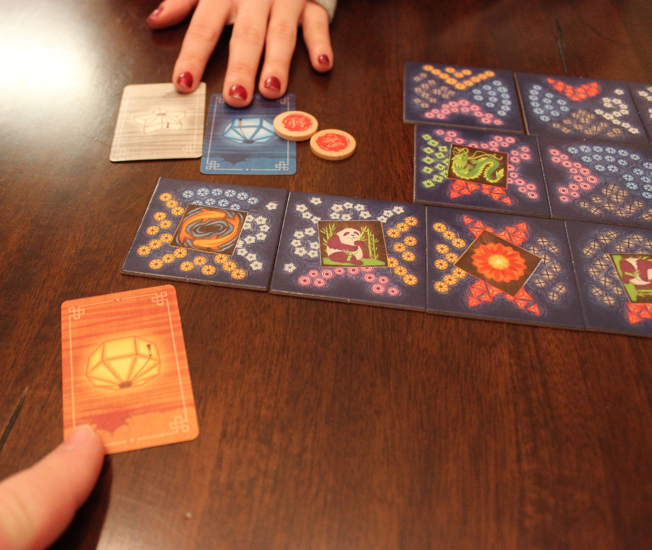 Here, the player across the table has placed a lake tile with the fish platform next to the tile with the panda platform. That player gets a blue card (because the blue faces her) and a white (because she matched a white side with a white side). She also gets two favor tokens for matching two platforms. Meanwhile, the second player across the table gets an orange card (because the orange faces him).