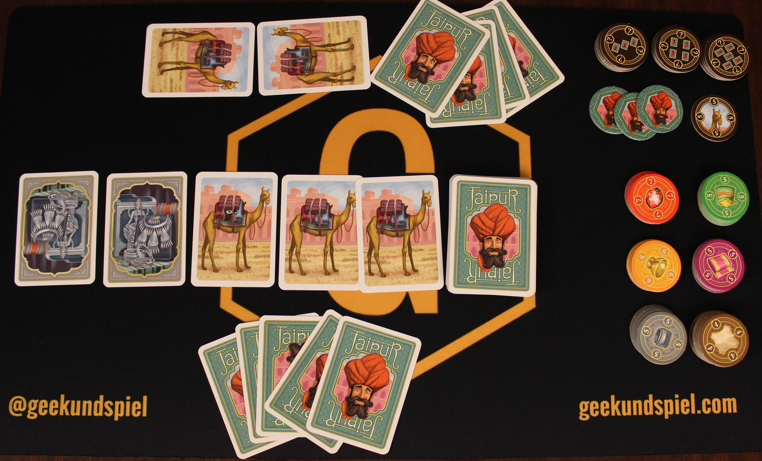 Game setup. Notice how the bottom player has no camels, but the top player is starting with two. The chips for sold cards are on the right, the bonus chips are at the top, and the three green chips with the person's face are given out for each round one.
