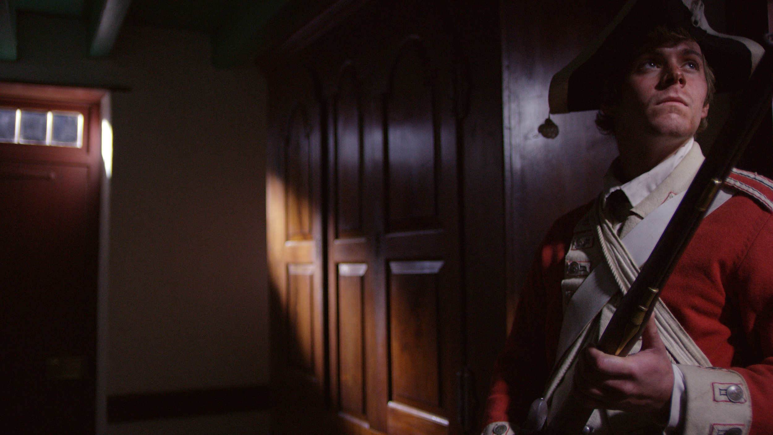 "Redcoat soldier, ""James,"" looks for valuables."