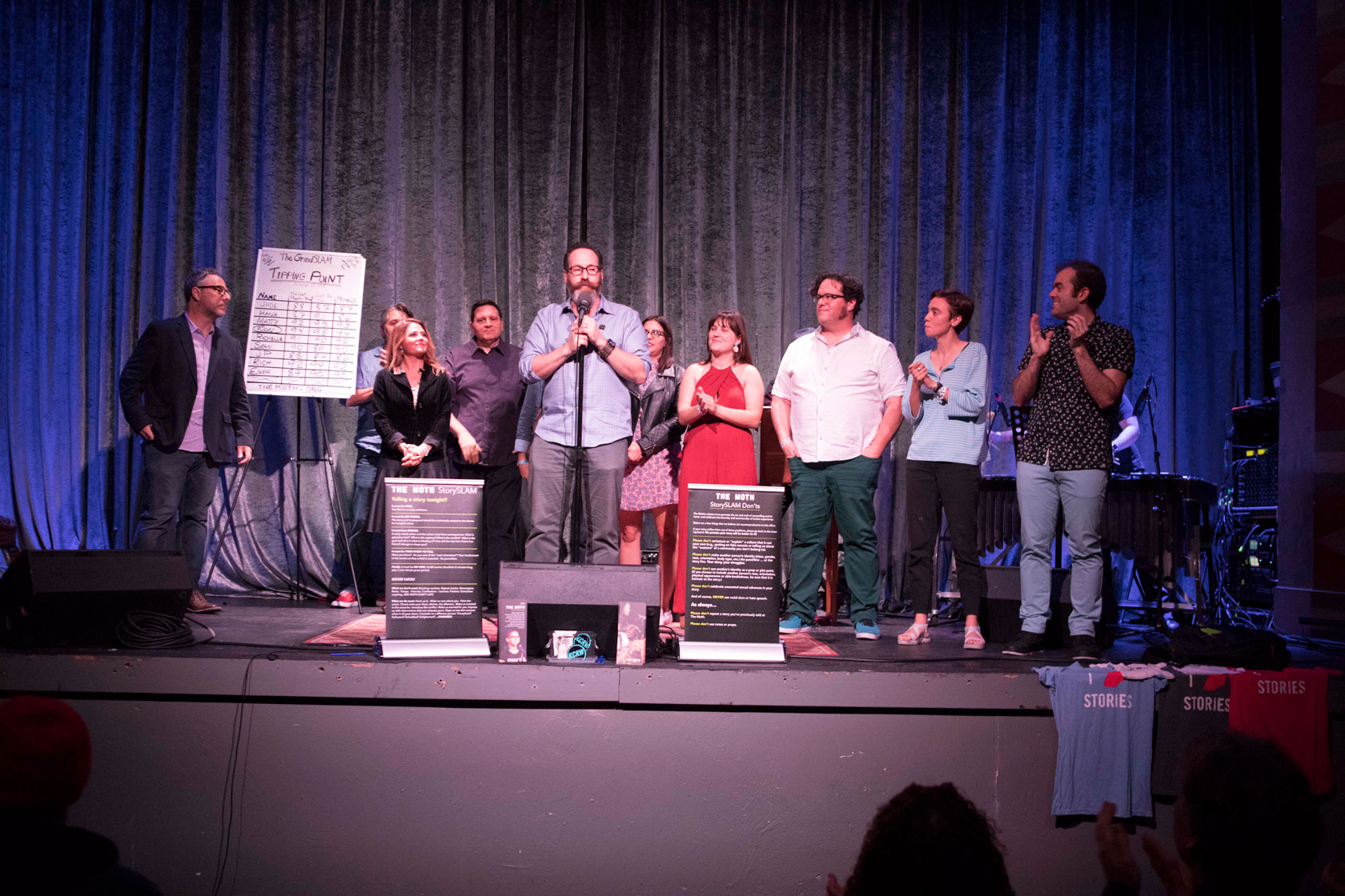 The evening's storytellers receive a warm round of applause at the conclusion of another Moth GrandSLAM in Los Angeles, October 22nd, 2018. (From left to right: Host Brian Finkelstein, storytellers Matthew Struski, Jade Driggers, Rich Tackenberg, StorySLAM producer Gary Buchler, Richelle Meiss, Hana Nobel, Ron Hart, Emma Horn & me.) Photo credit: Ricky Steel, courtesy of The Moth.
