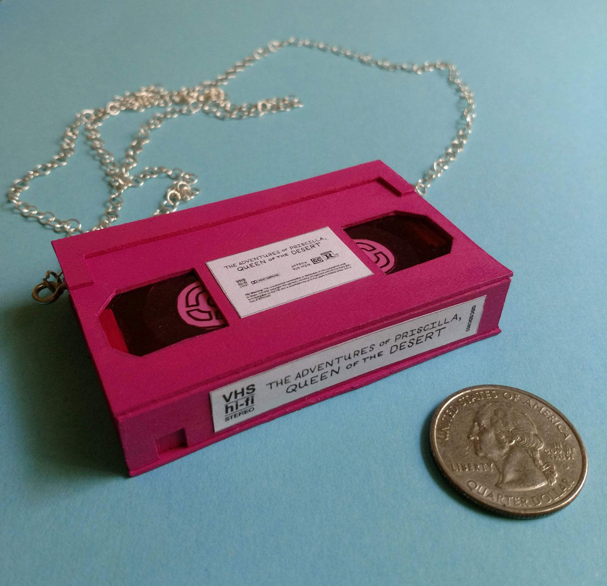 """Queer Sleepover Classics"" miniature VHS pendant necklace; Balsa wood, construction paper, acrylic paint, eye hooks & chain"