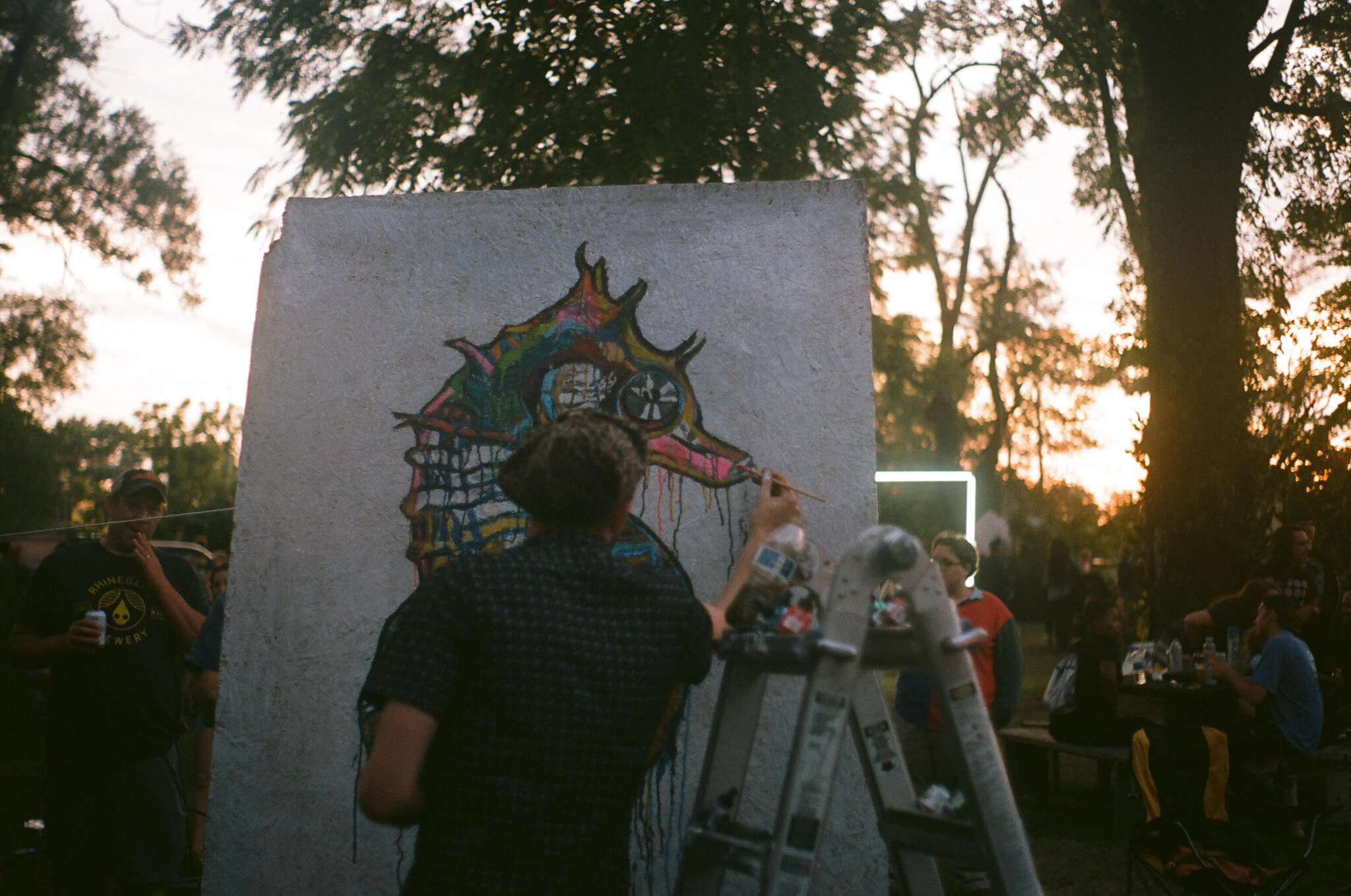 Russell Frantom  works on a large-scale painting amidst the crowd.