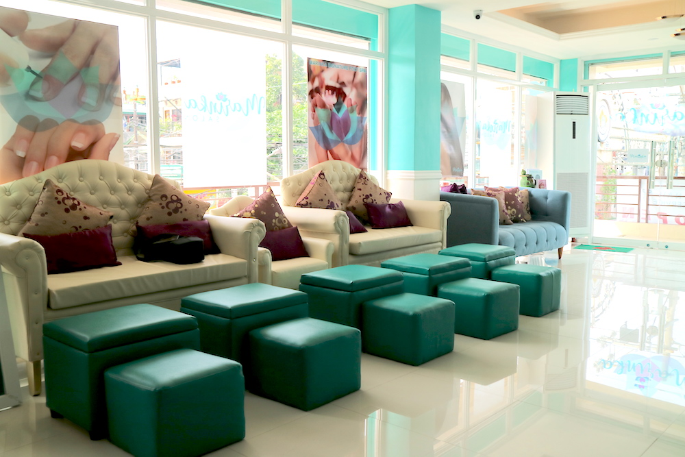 One whole side of the salon is floor-to-ceiling window panes, creating a bright and airy ambiance