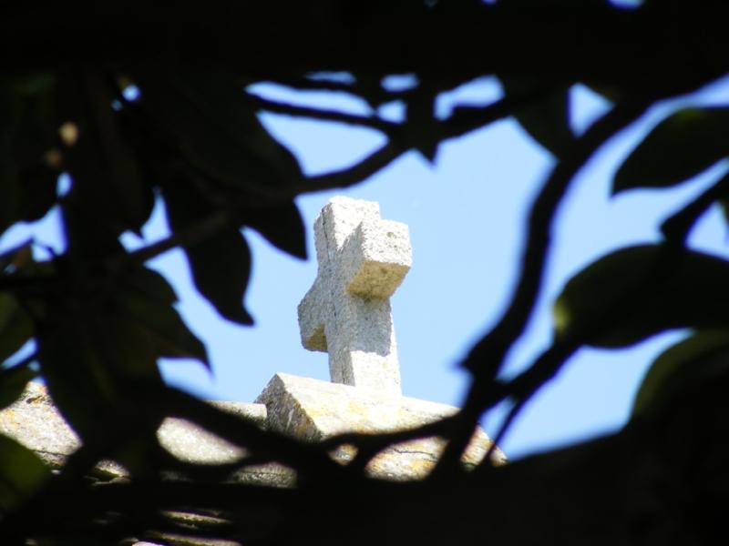 Cross on chapel through the trees