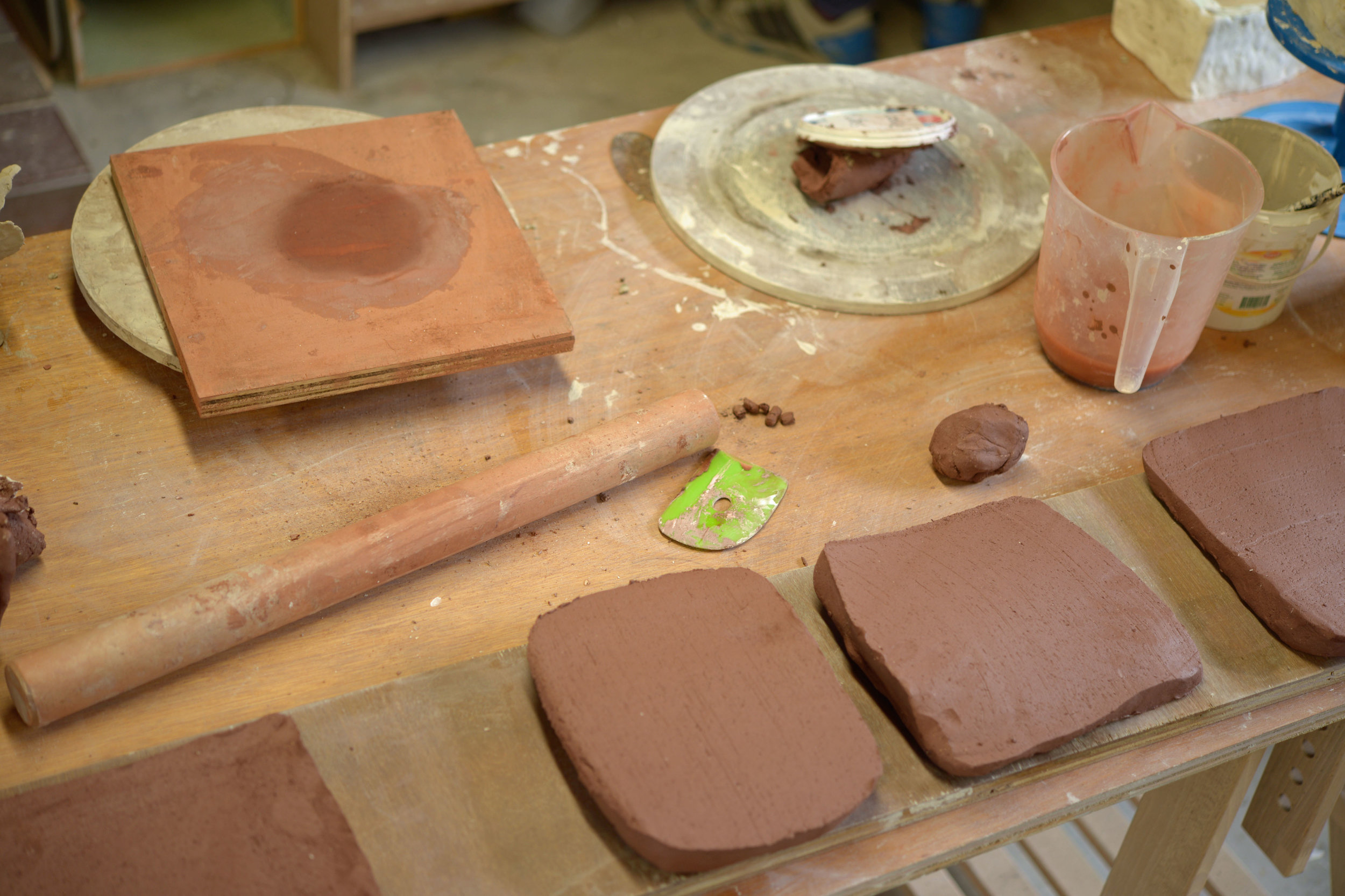 Firstly we roll out thick slabs of dark clay