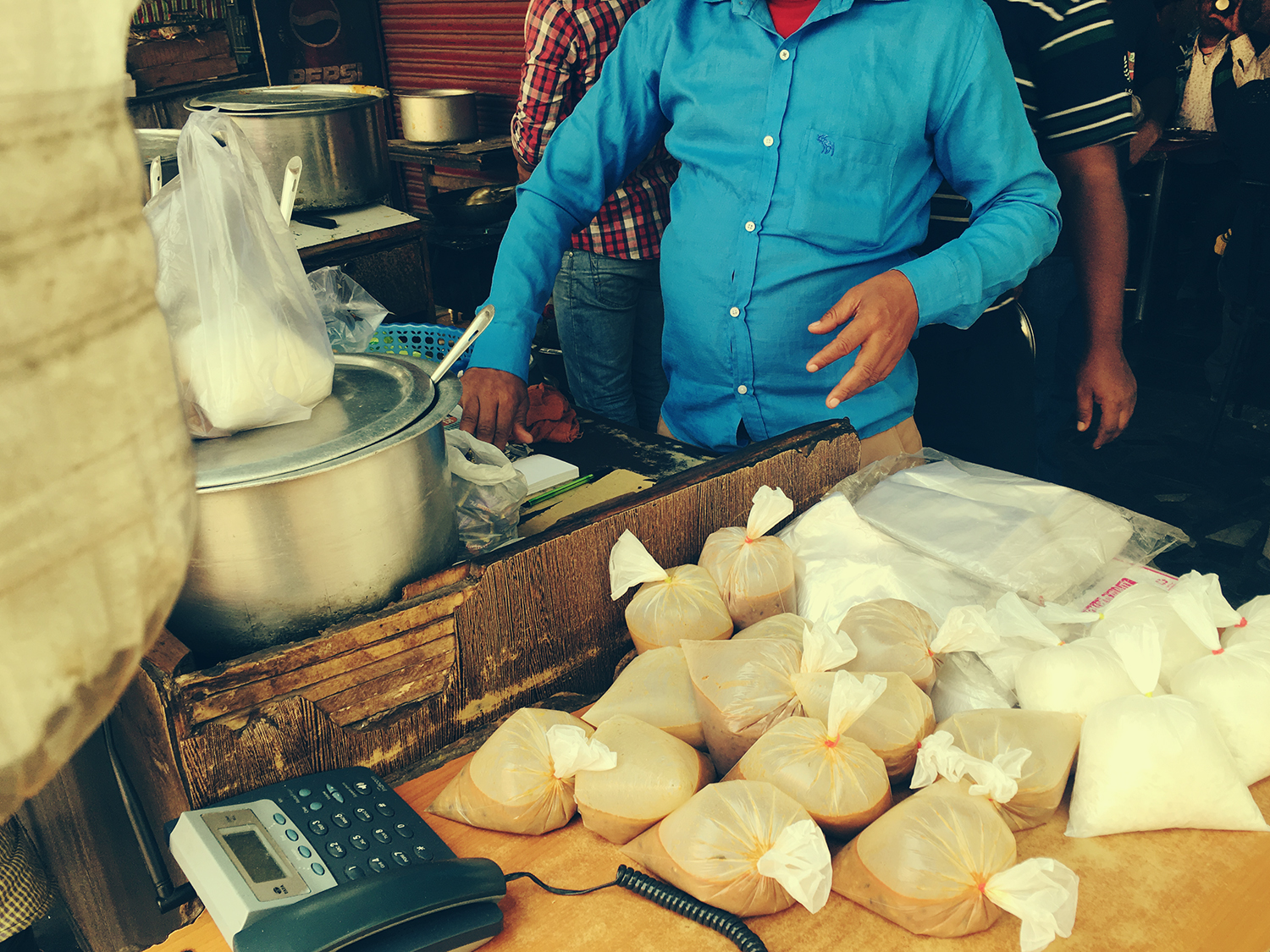 Street vendor with bags of rice ready to  go with the paneer curry stewing in the large metal pot