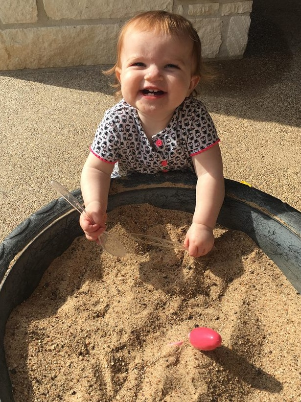 happy baby playing with sand
