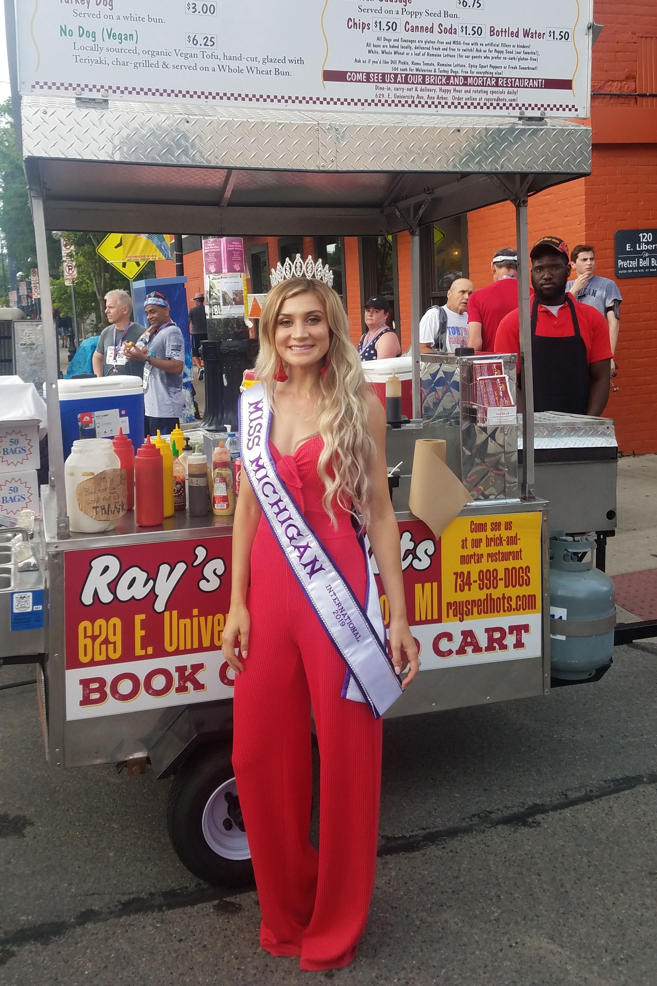 Miss Michigan International 2019 stops by to get her mom a dog at the Firecracker 5k / Fourth of July Parade in downtown Ann Arbor.