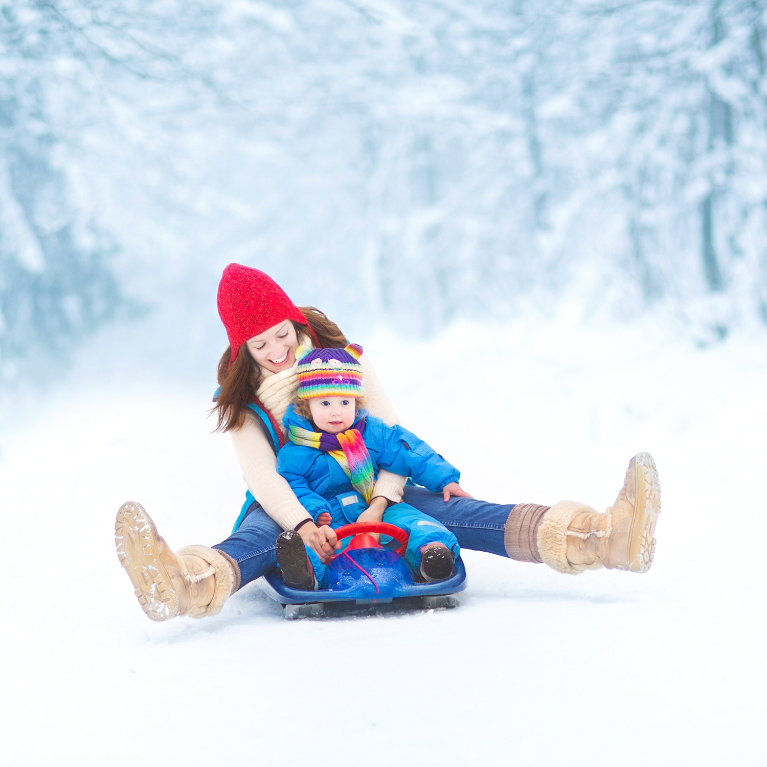 Mother-and-toddler-daughter-enjoying-sledge-ride-in-snowy-park-000038408102_Large.jpg