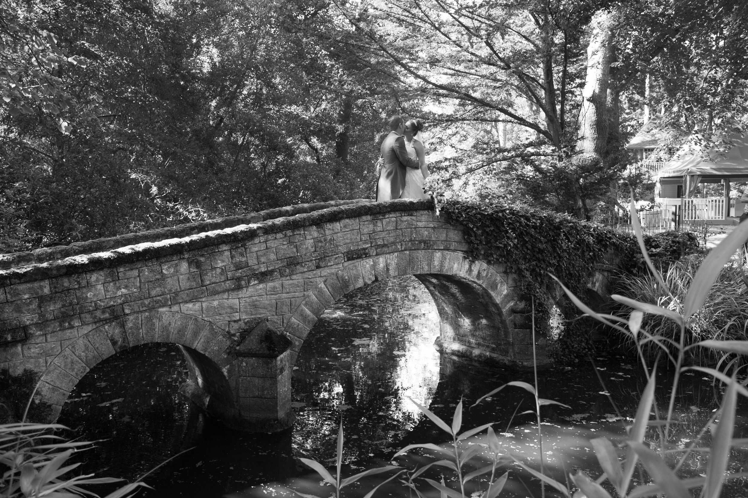 Bride and Groom kiss on the stone bridge Hogarths Hotel Solihull