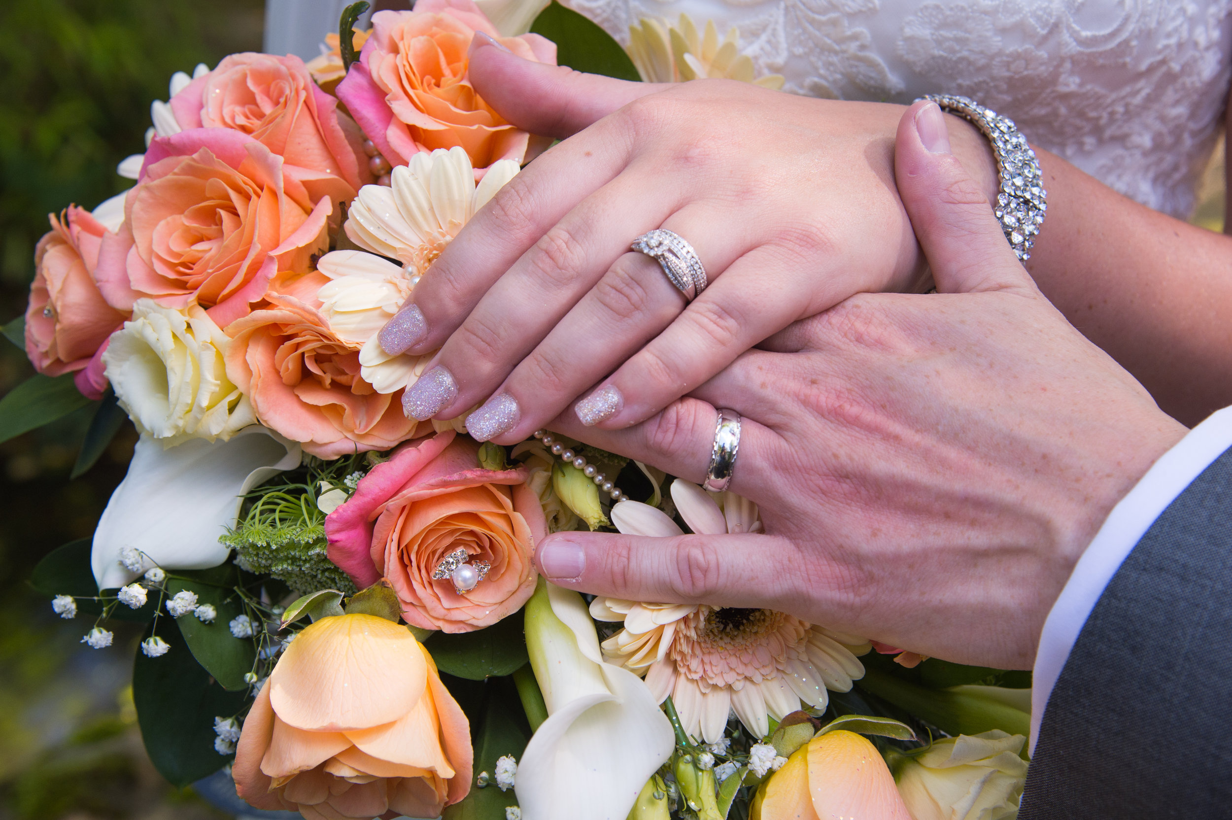 Bride and Groom hold hands over wedding bouquet
