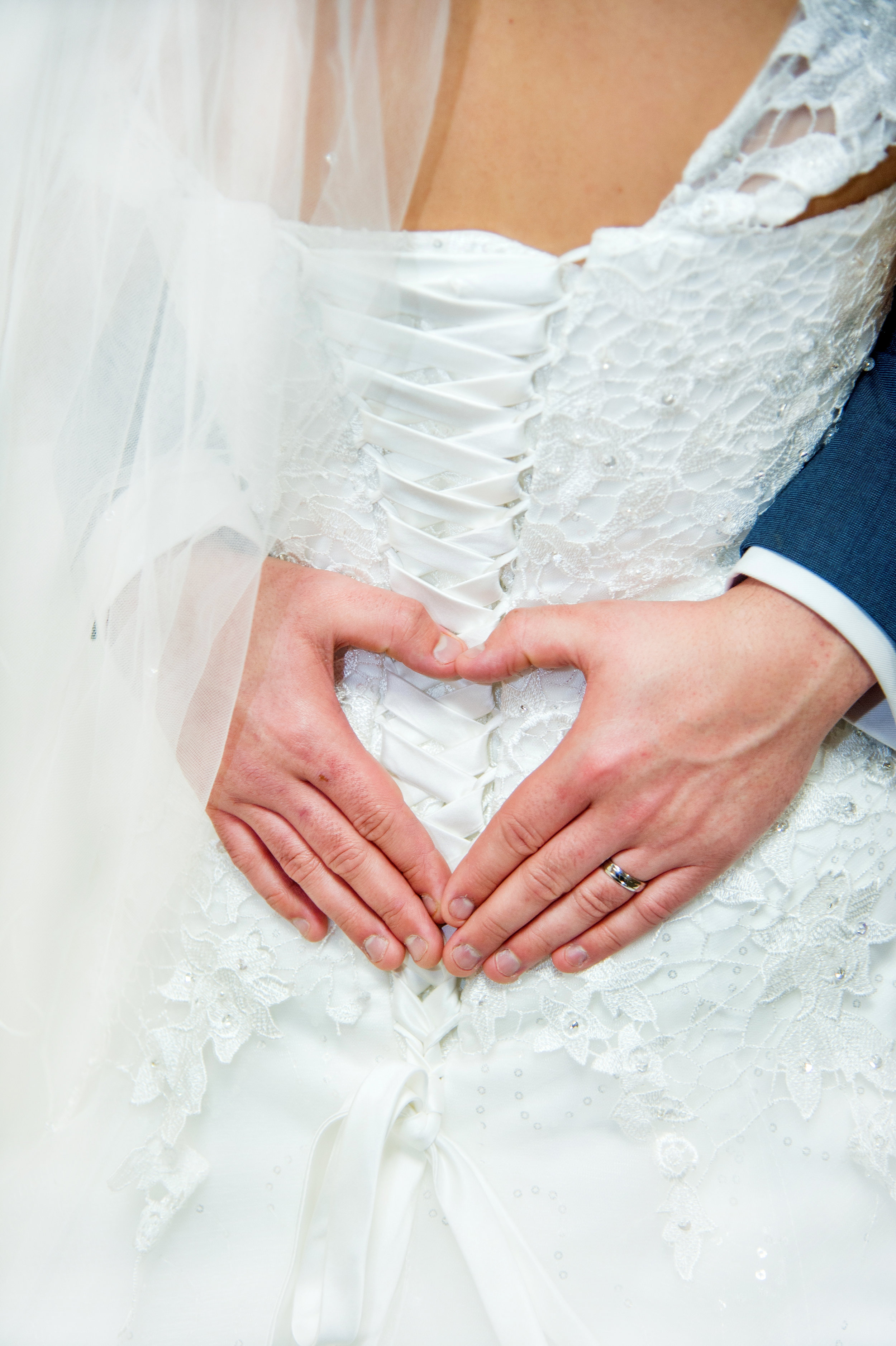 Groom making hand heart on wedding dress