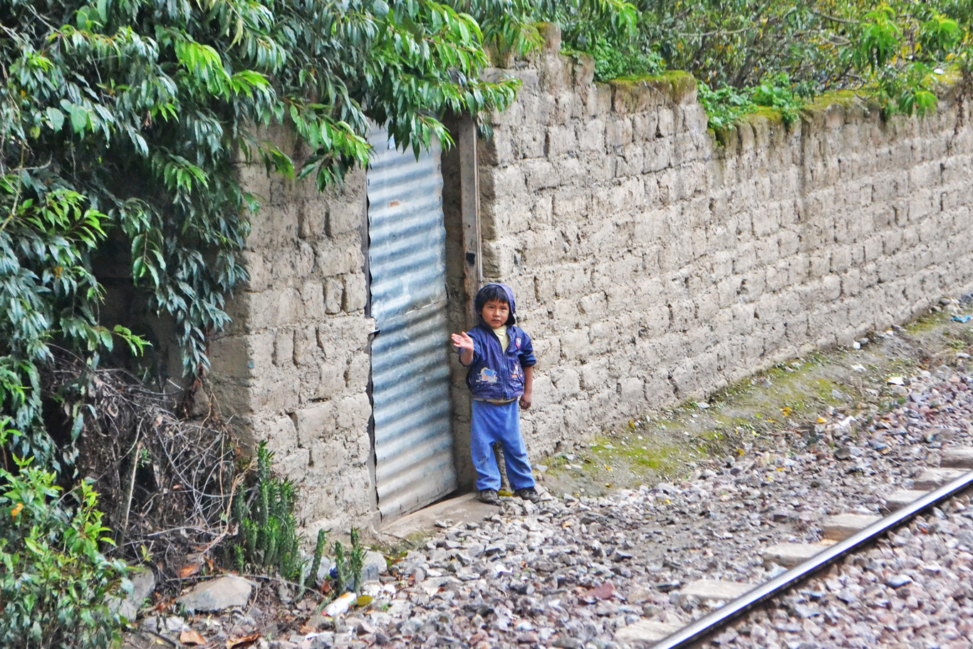 A boy waving at the train to Machu Picchu