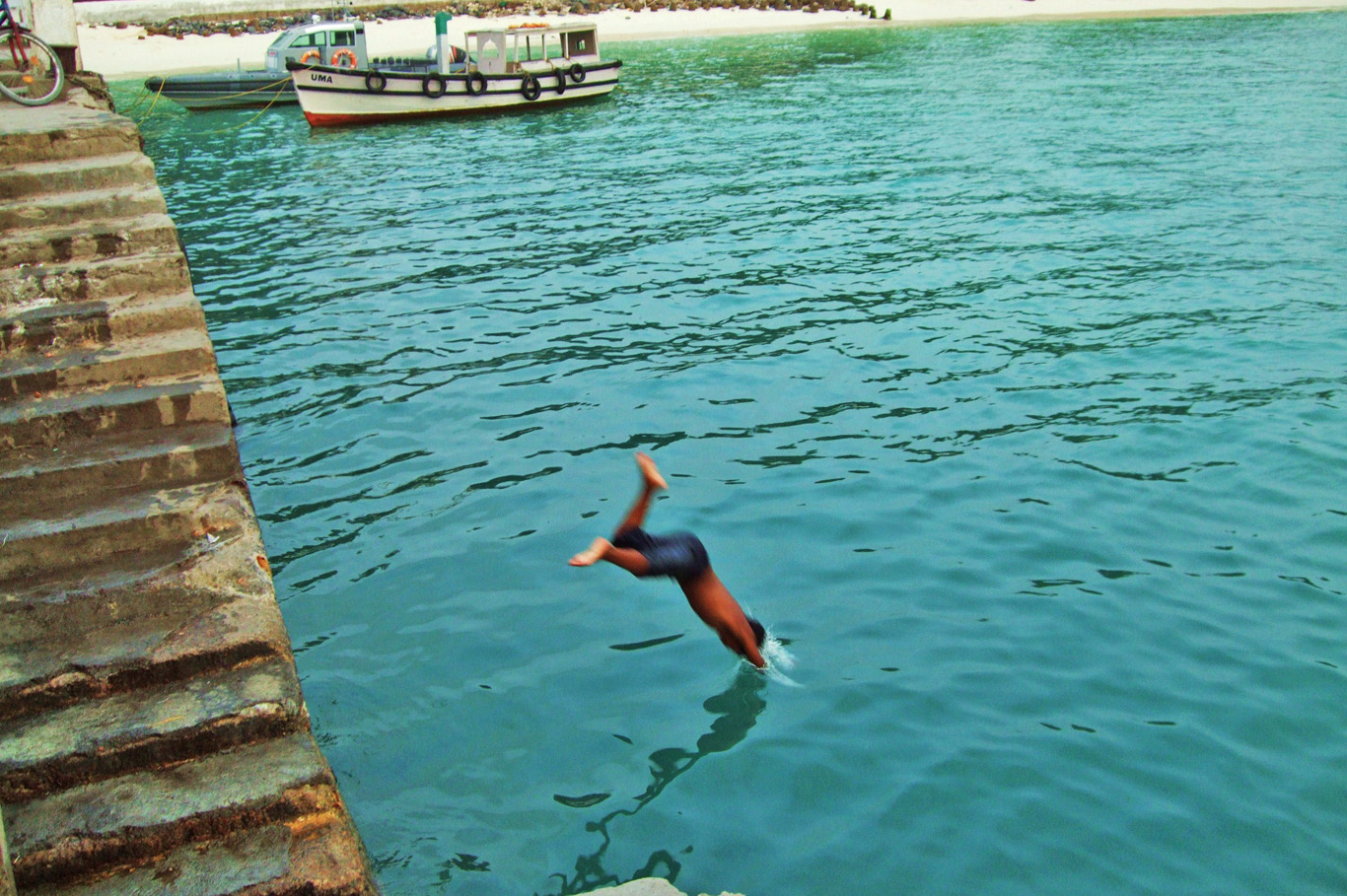 Local boy jumping into the sea