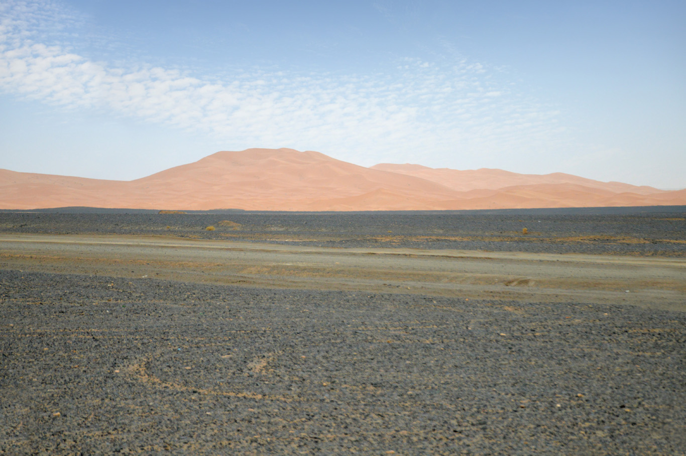 Moon-like, barren landscapes and dunes emerging on the horizon
