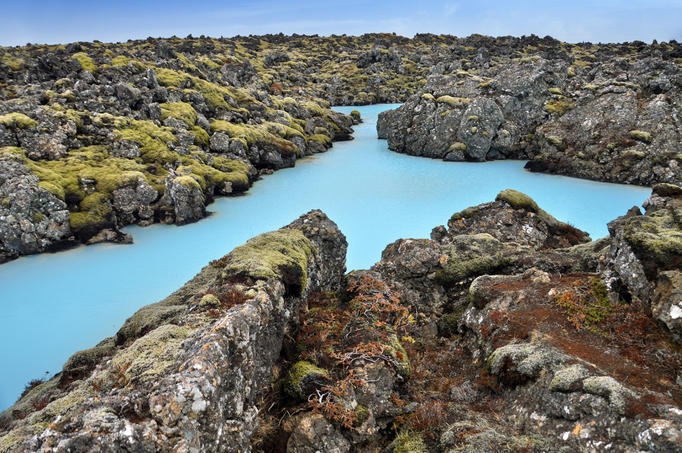 Blue pool among volcanic rock