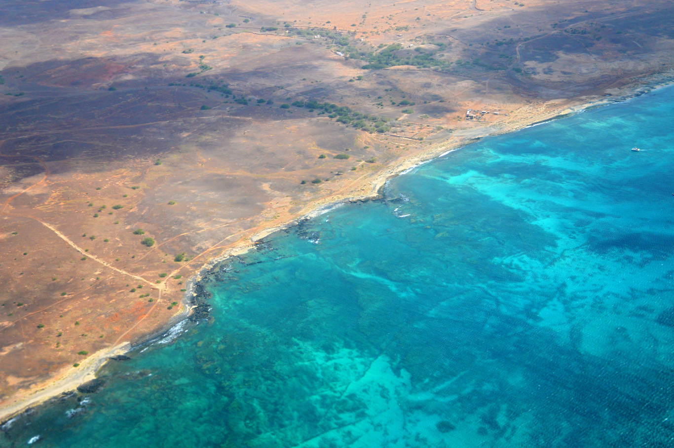 Dry land and turquoise water - view from the plane
