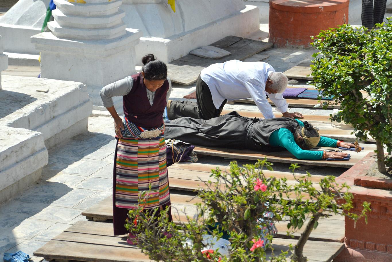 Worshipers praying in front of Boudhanath Stupa