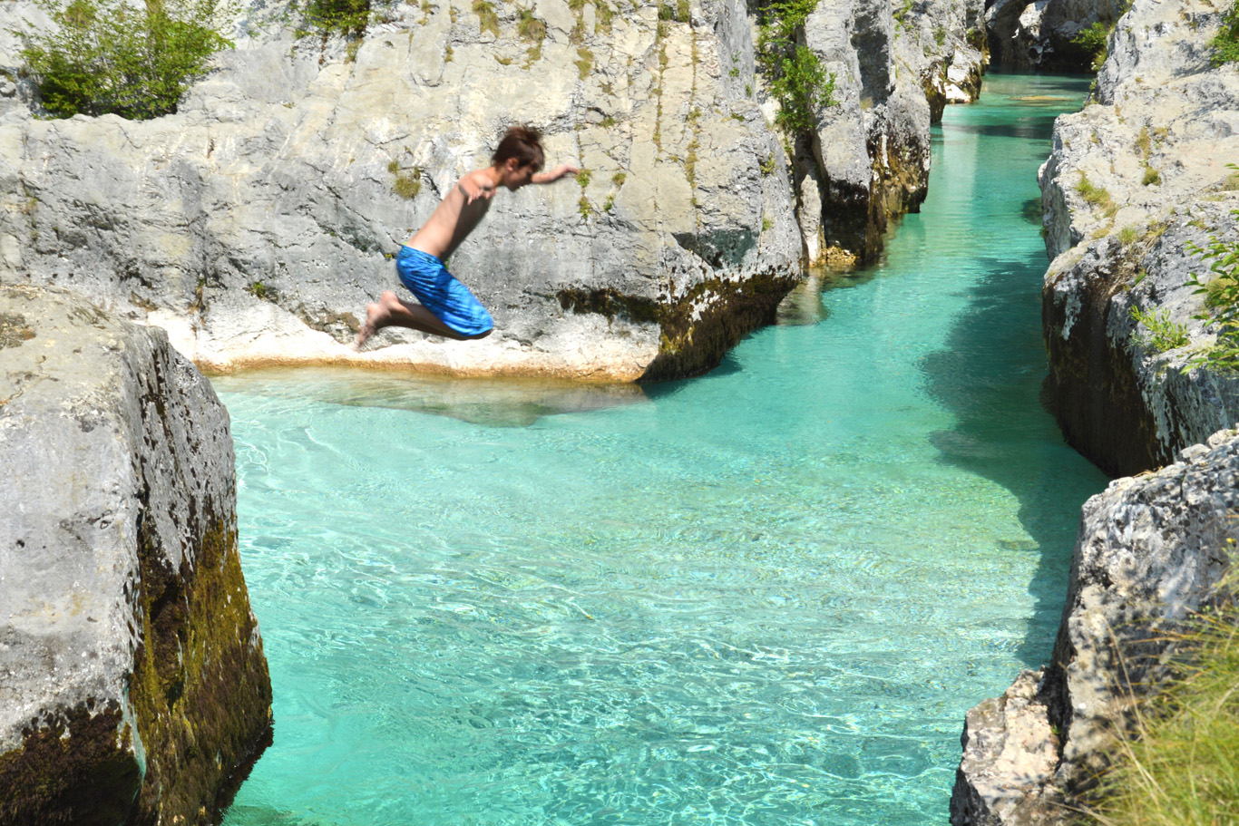 A boy jumping into the turquoise waters of Soca River