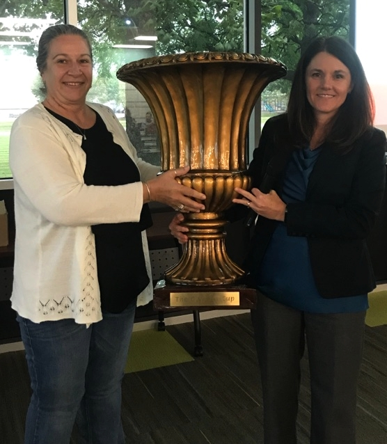 Krisi Schell (right), Organizational Development Manager at SRC Holdings, presents the traveling Owners' Cup trophy to Leslie Booker (left), Open-Book Committee Chair of CNHi Reman.