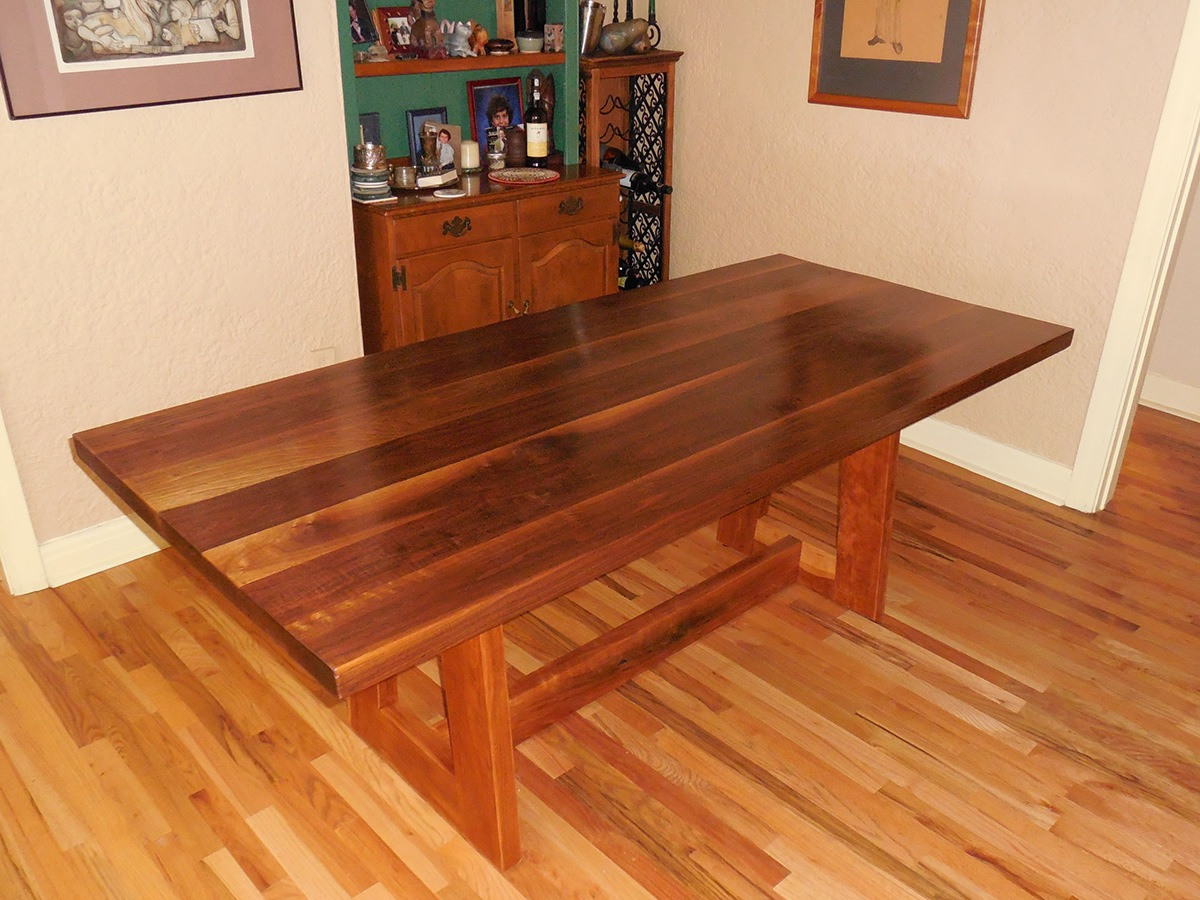 Dining room table seats 6-8. Walnut top. Cherry base with trapezoid shaped trestle legs.