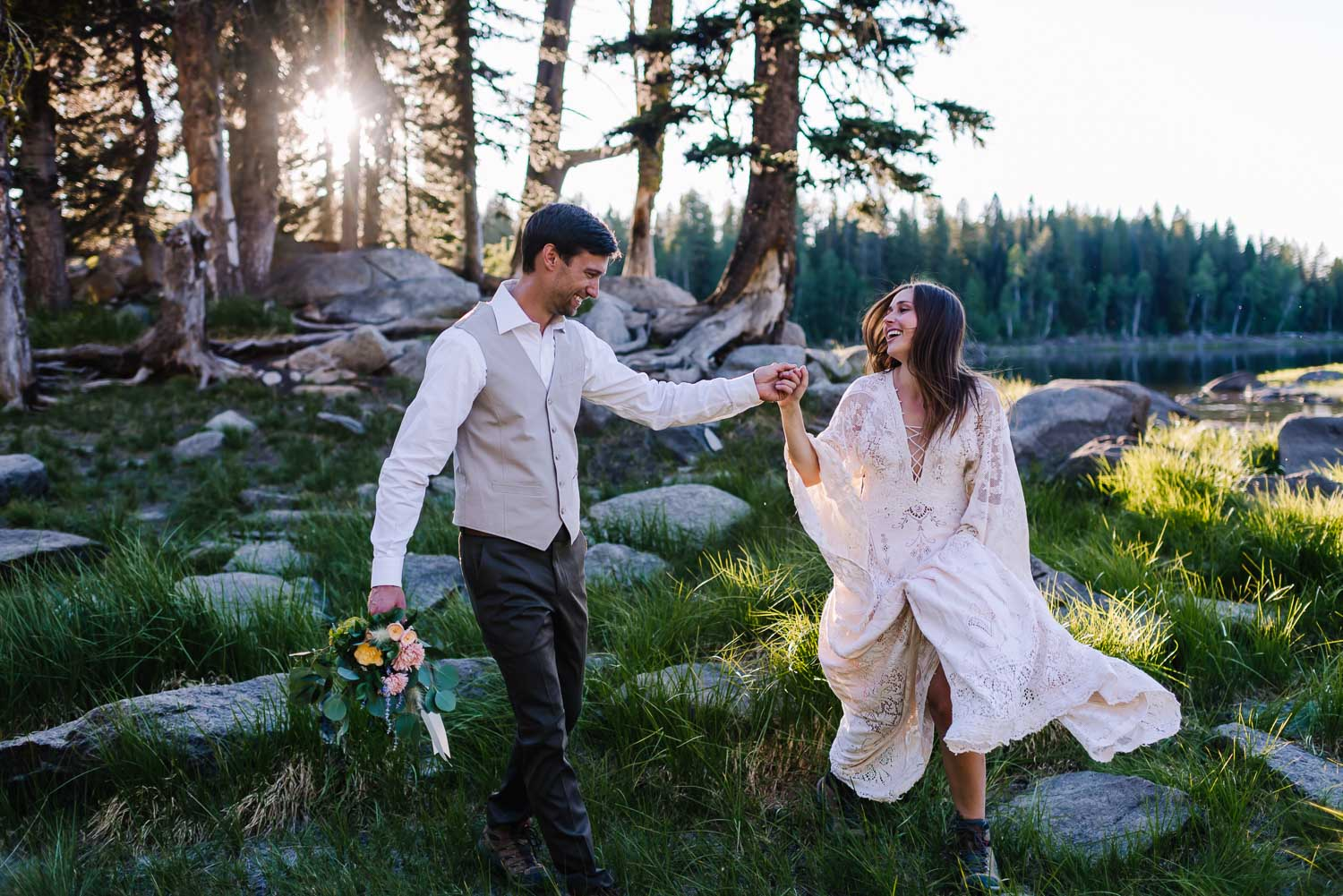 Louie Lake is an adventurous wedding venue in McCall Idaho. Couple running along the lake holding hands.