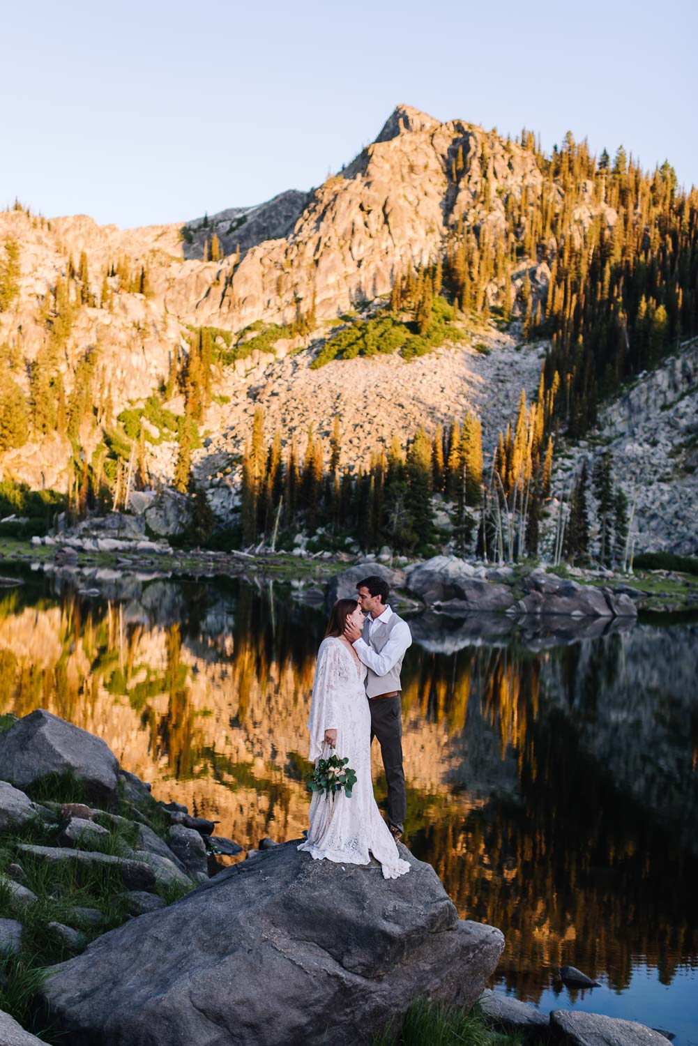 Louie Lake is an adventurous wedding venue in McCall Idaho. Couple standing on rock with Jughandle Mountain behind them and reflecting on the lake.